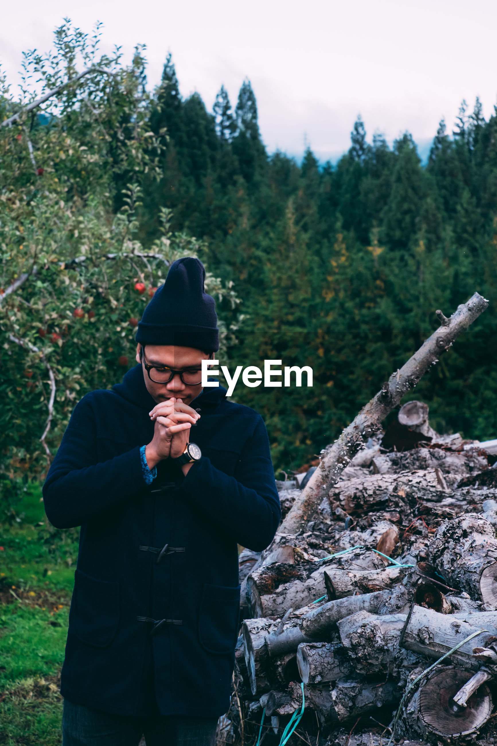 Man praying while standing against logs in forest