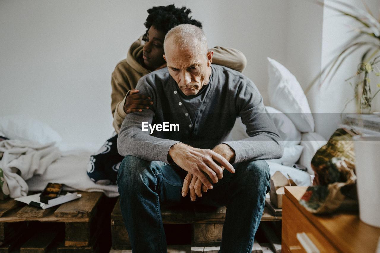 MEN SITTING ON SOFA AT HOME