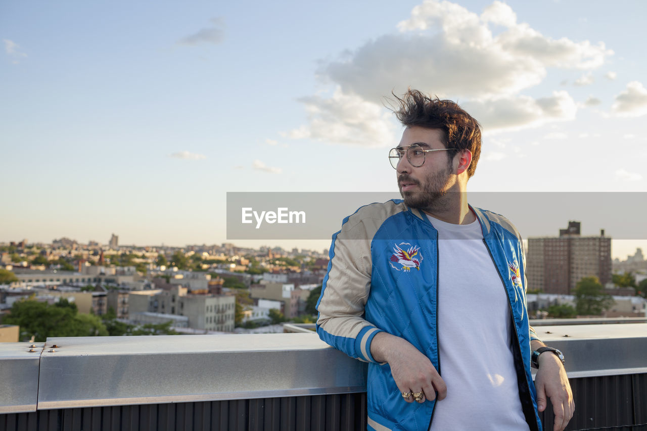 sky, architecture, standing, building exterior, built structure, young men, city, young adult, waist up, front view, one person, glasses, lifestyles, beard, nature, leisure activity, real people, focus on foreground, cityscape, outdoors, contemplation