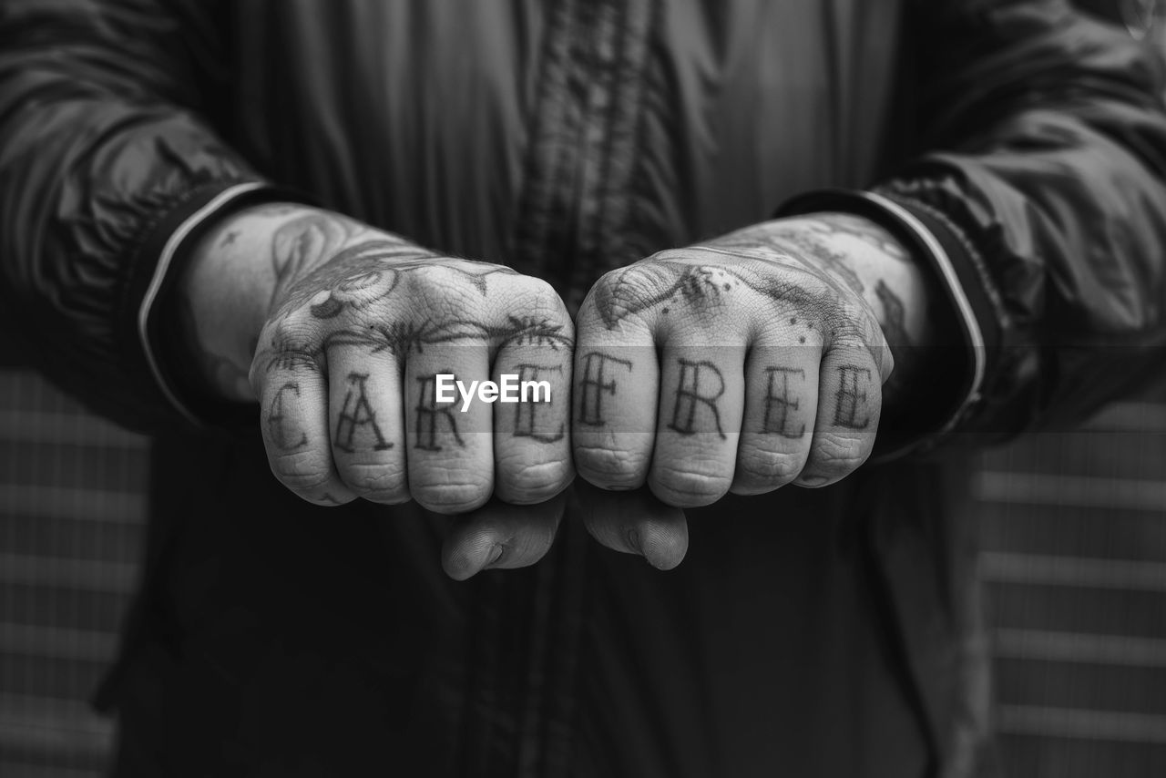 CLOSE-UP OF MAN HAND WITH TATTOO