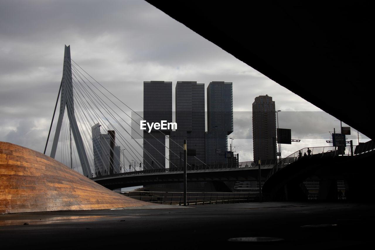 BRIDGE BY BUILDINGS AGAINST SKY