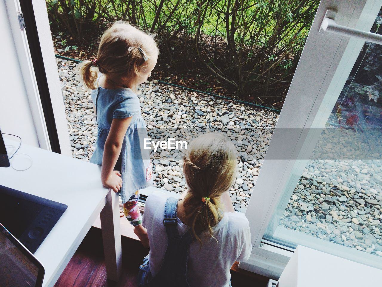 High Angle View Of Mother With Daughter By Window At Home