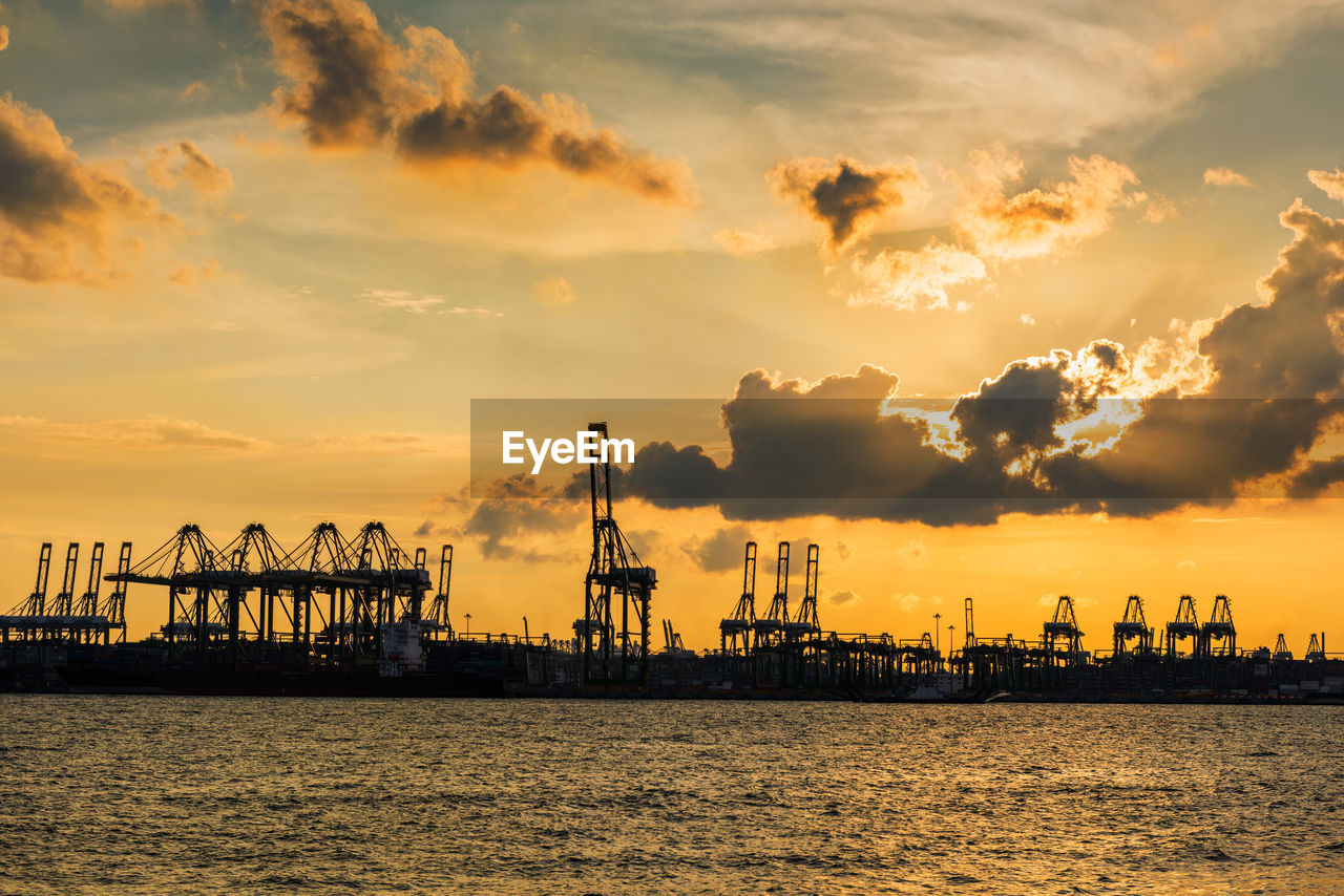 sunset, water, sky, cloud - sky, machinery, waterfront, freight transportation, industry, crane - construction machinery, sea, commercial dock, architecture, pier, nature, transportation, business, harbor, orange color, nautical vessel, no people, outdoors, construction equipment