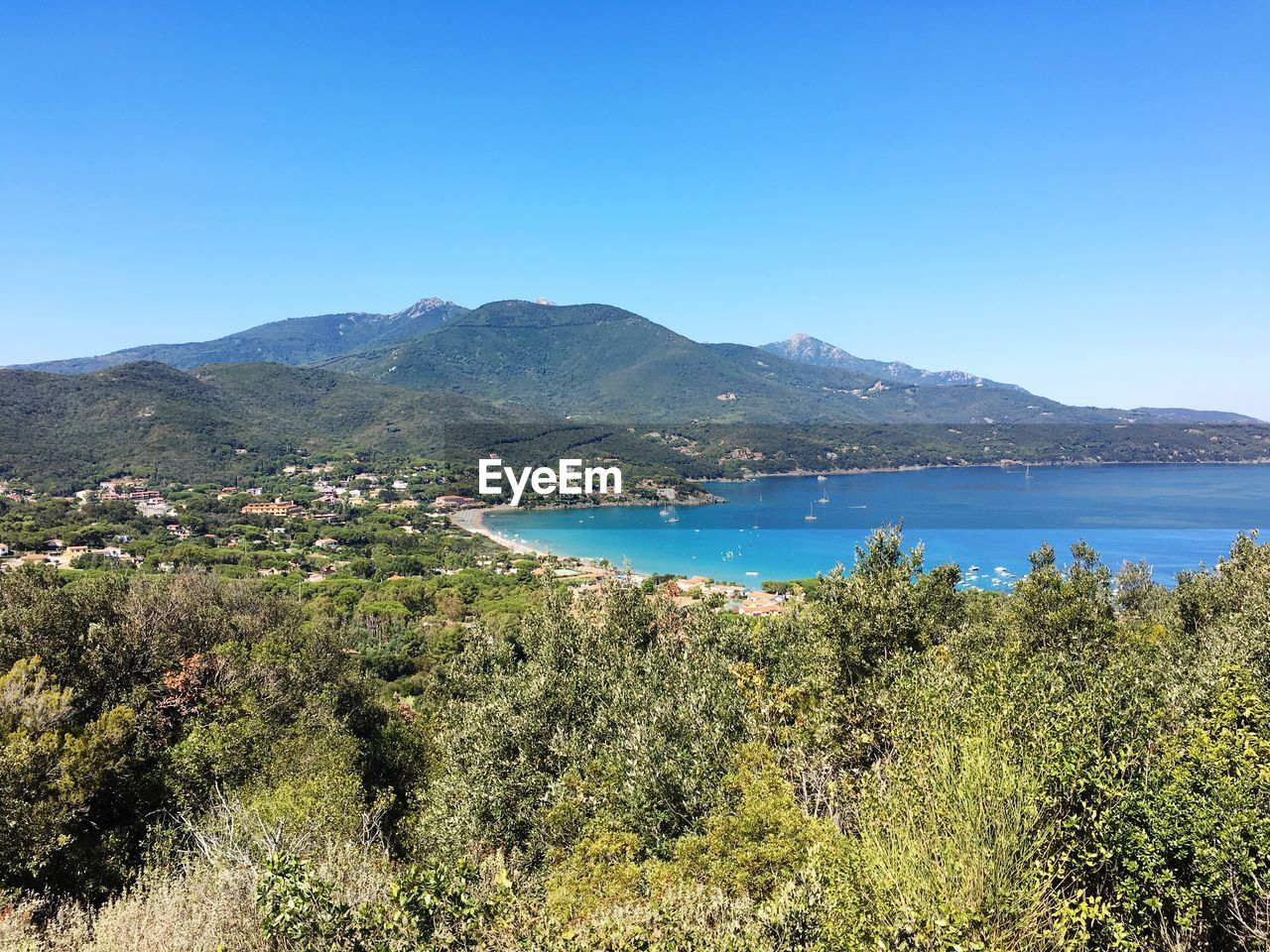 mountain, nature, clear sky, tranquil scene, beauty in nature, tranquility, outdoors, scenics, blue, day, no people, mountain range, architecture, water, landscape, sea, town, tree, sky