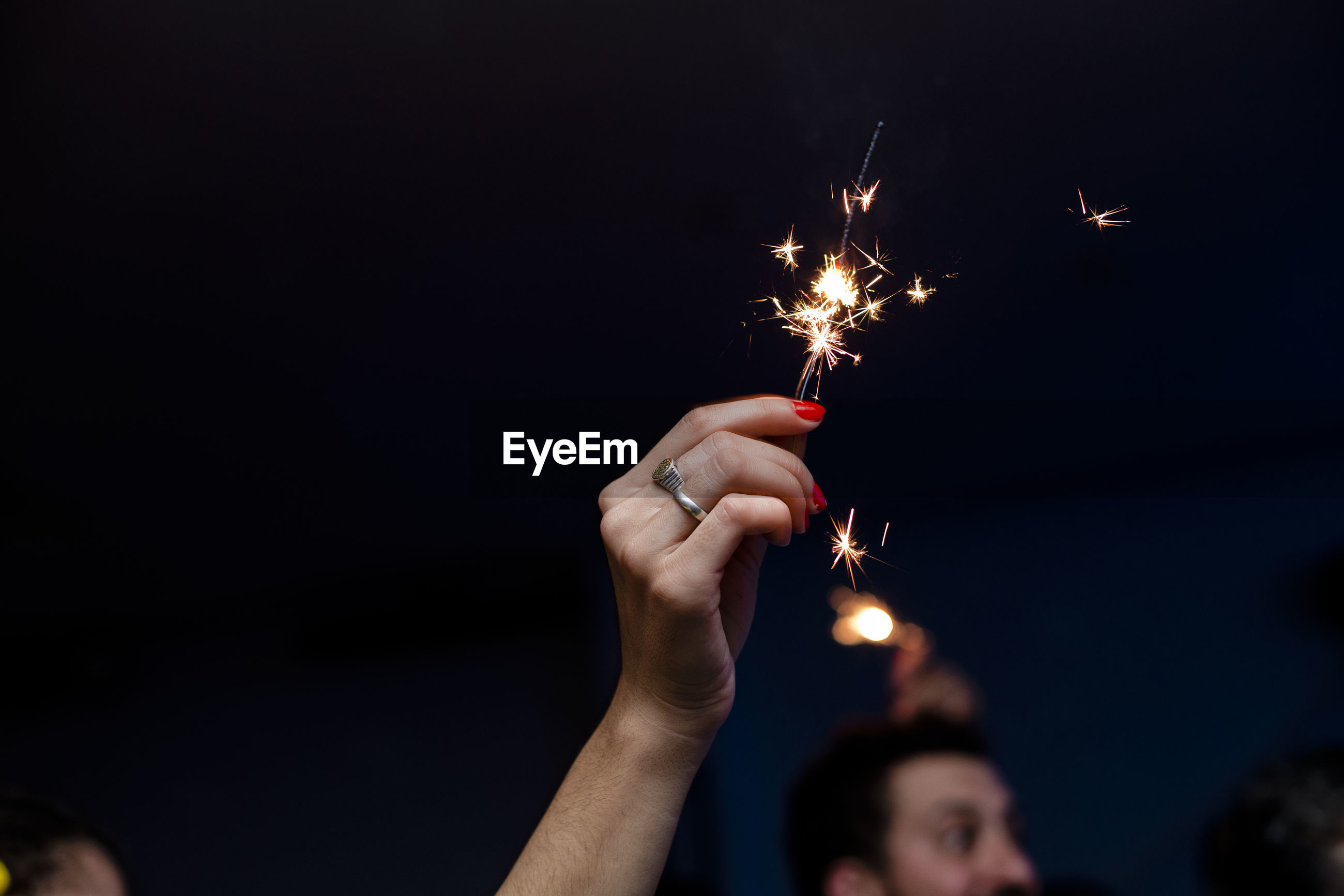 Cropped hand of woman holding lit sparkler at night