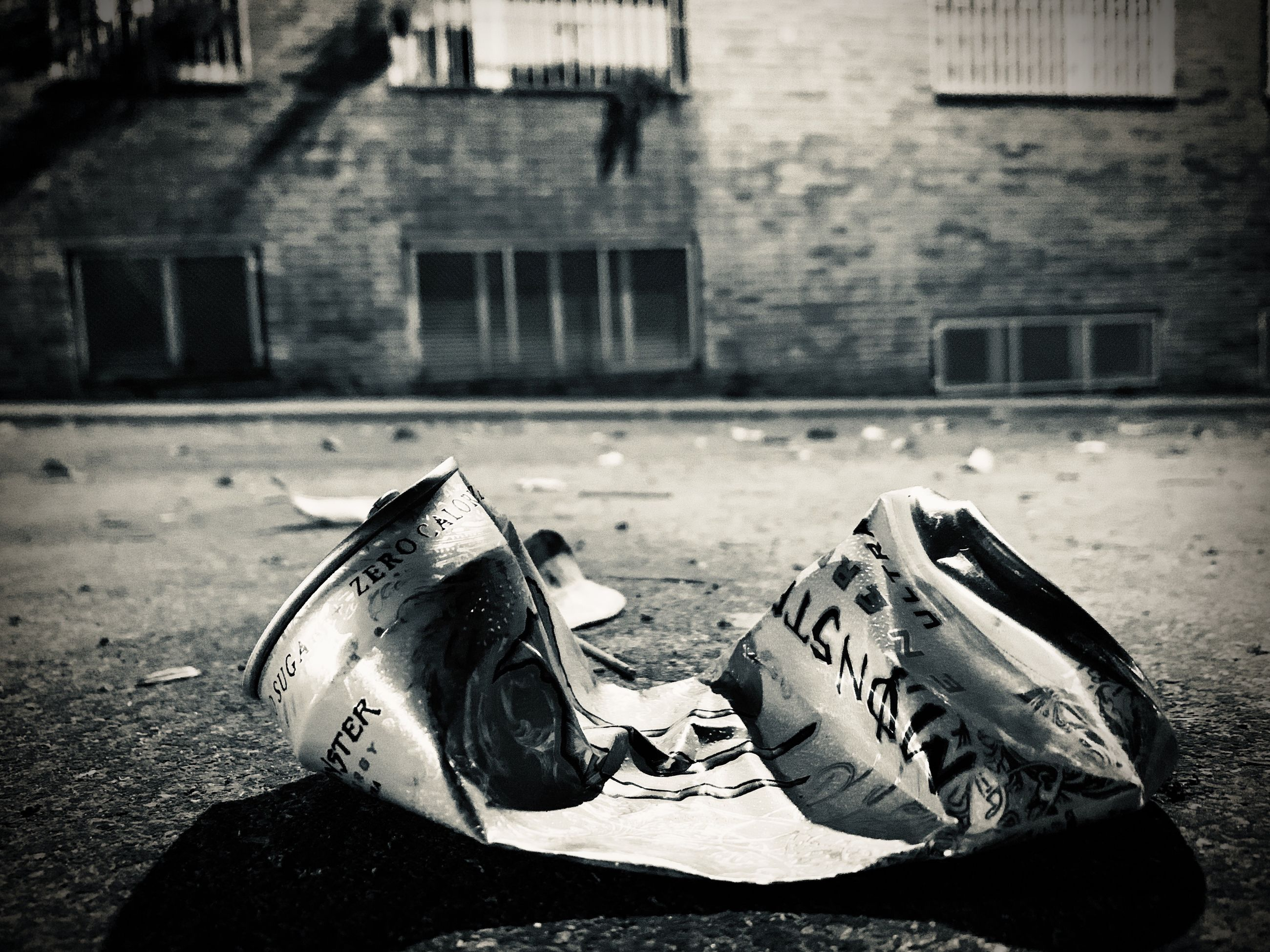 CLOSE-UP OF ABANDONED SHOES ON FOOTPATH AGAINST BUILDING