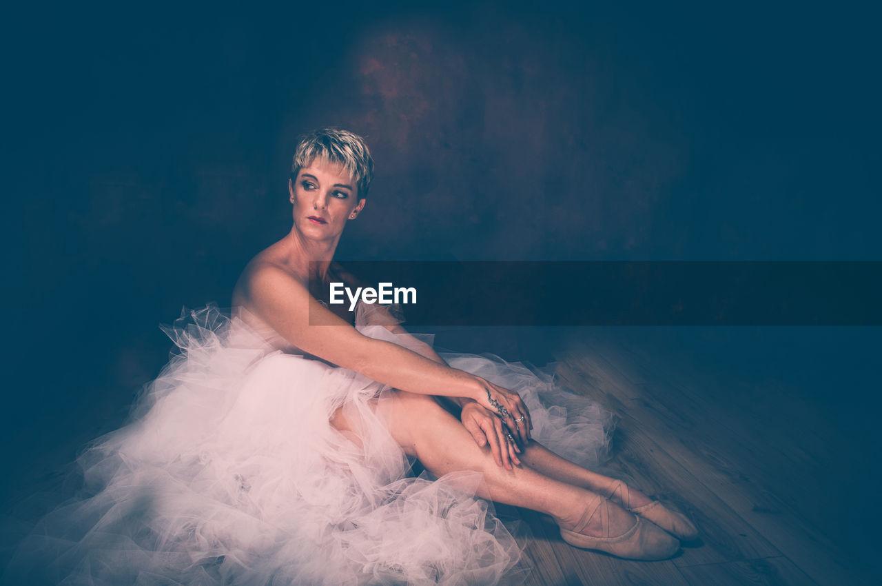 Semi-Naked Woman Wearing Tulle Tutu Against Black Background