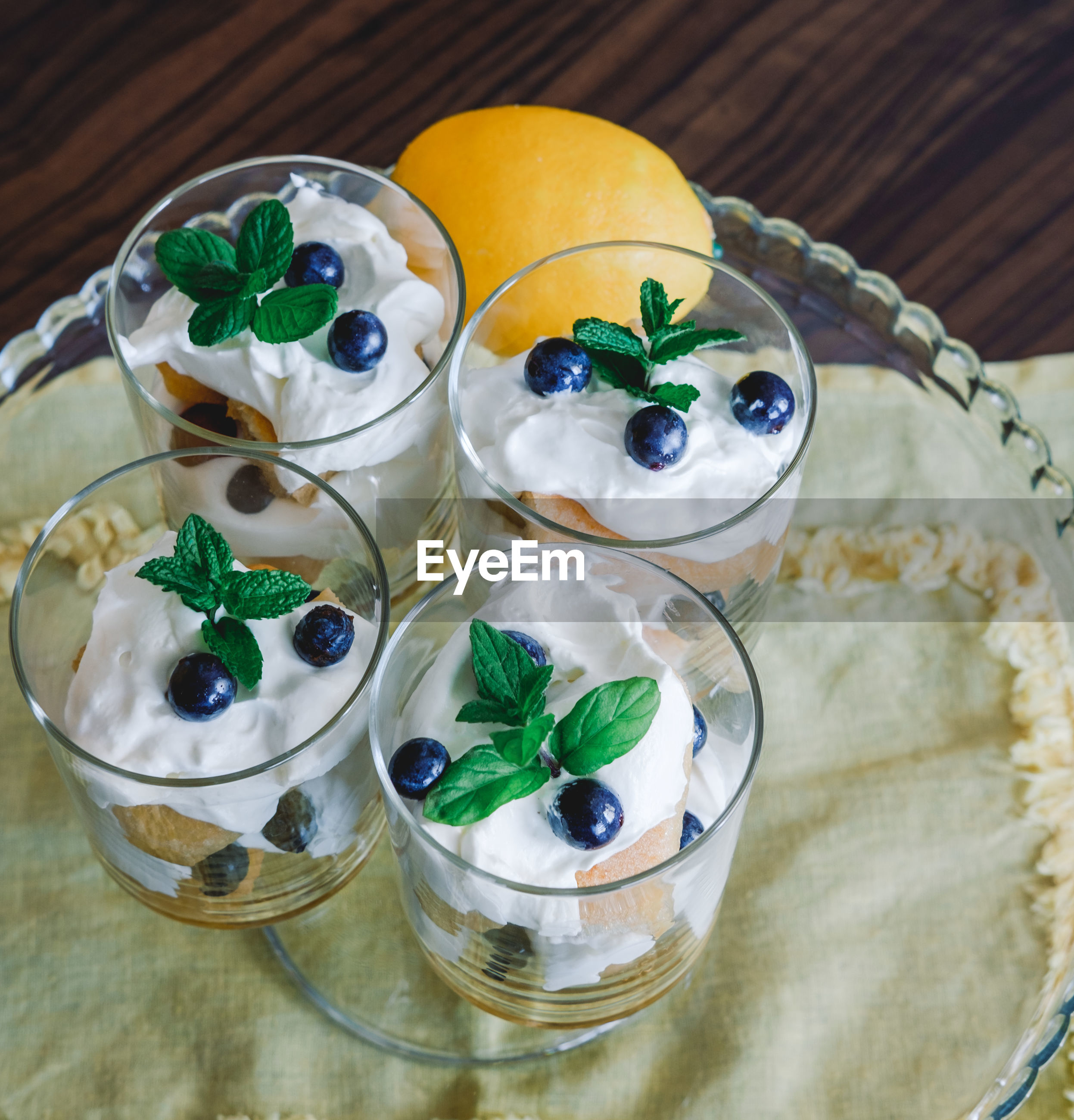 Homemade tiramisu with lemons served on table. top view of delicious dessert in glass cups.