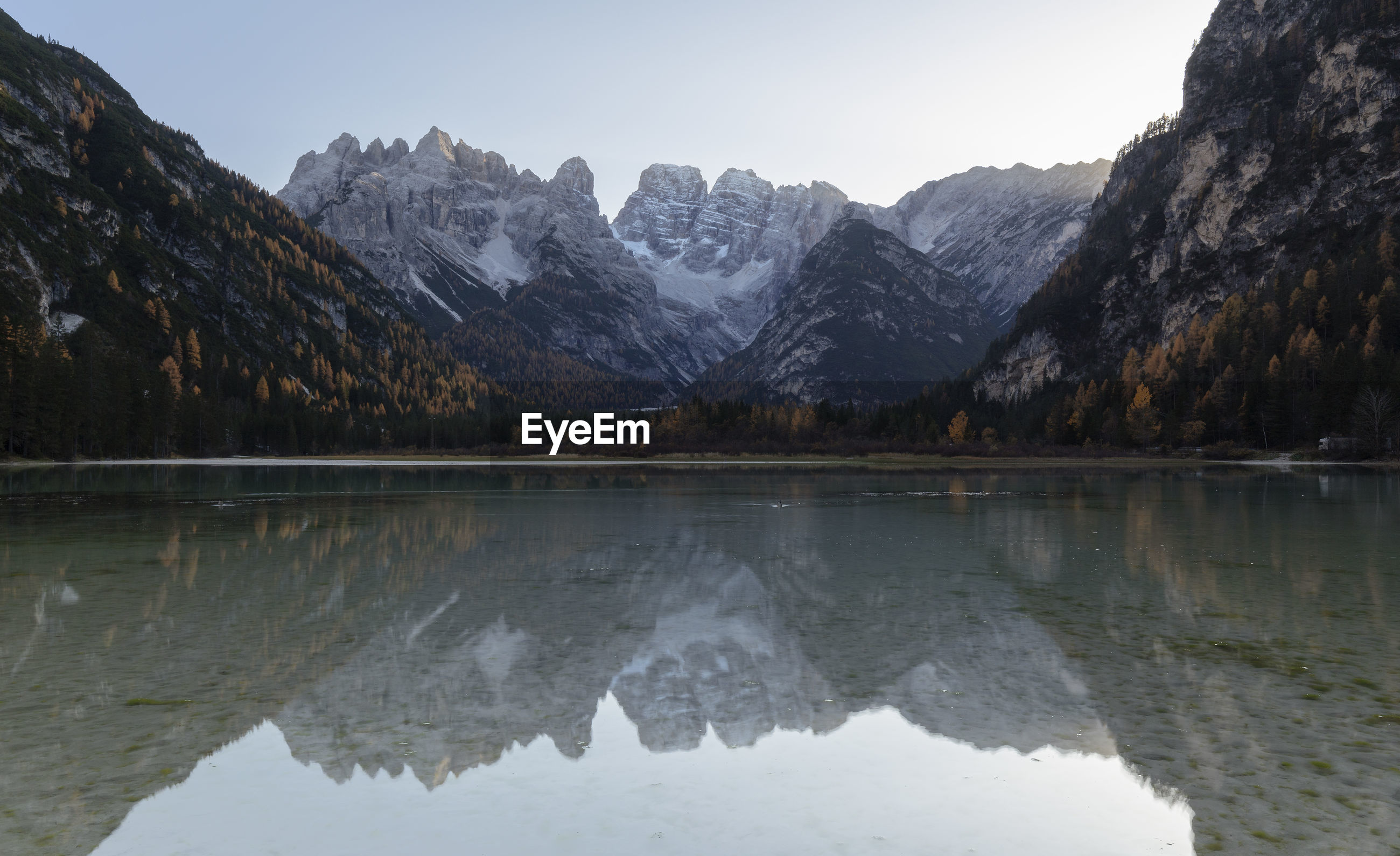 Scenic view of lake by snowcapped mountains against sky in dolomites mountains