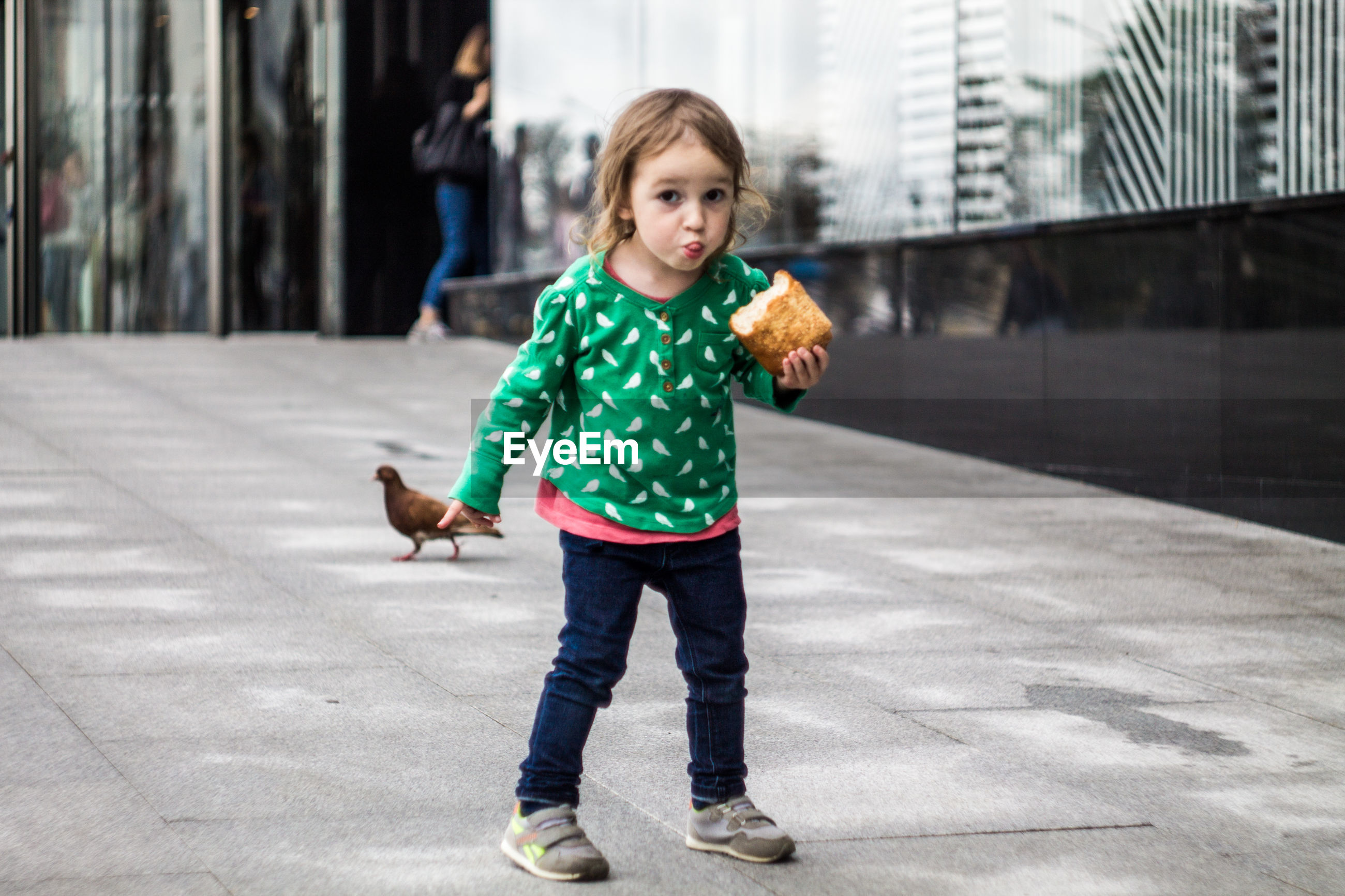 Portrait of cute girl eating bread while standing on footpath