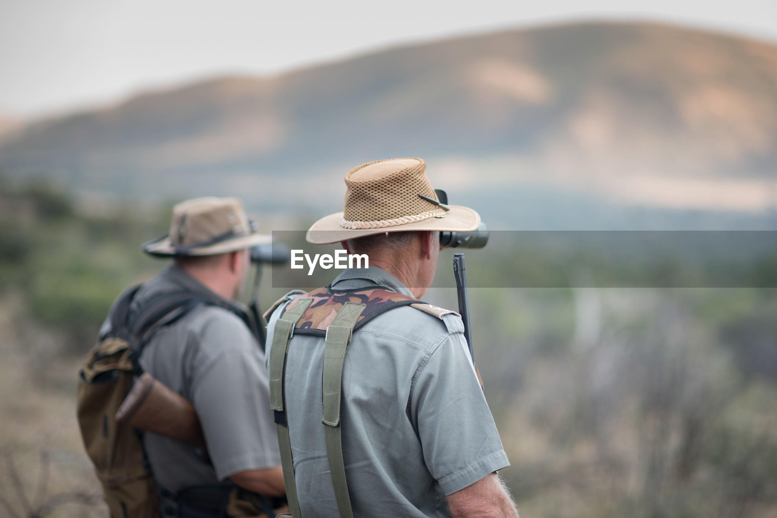 Side view of men looking through binoculars