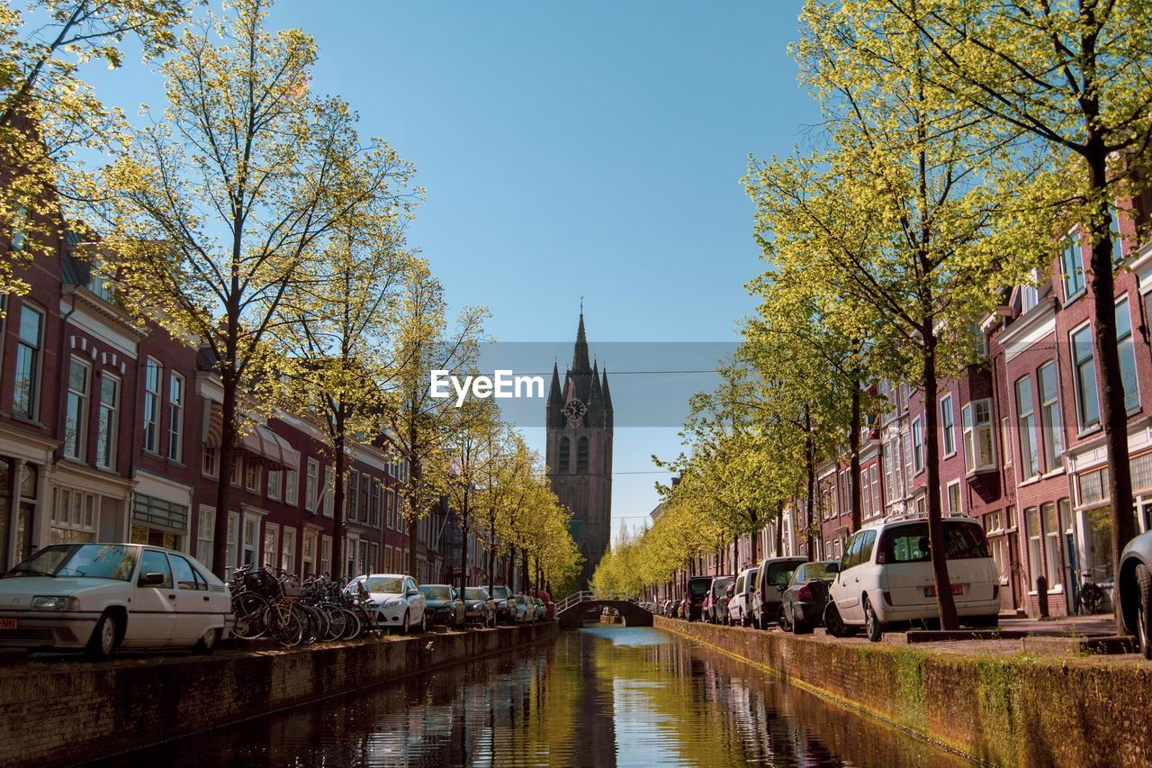 building exterior, architecture, built structure, mode of transportation, car, tree, motor vehicle, transportation, city, building, sky, land vehicle, plant, street, nature, day, residential district, incidental people, road, clear sky, outdoors, canal, row house