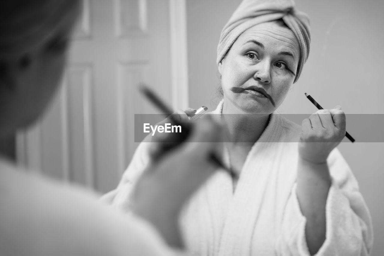 Mature woman applying make-up reflecting on mirror at home