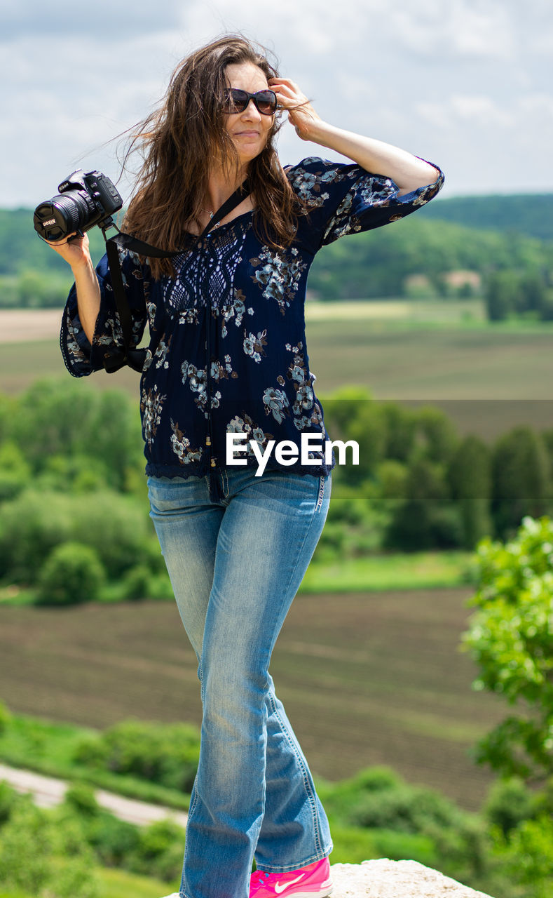 one person, real people, focus on foreground, leisure activity, hairstyle, lifestyles, casual clothing, young women, standing, young adult, hair, fashion, long hair, three quarter length, day, glasses, sunglasses, nature, brown hair, outdoors, beautiful woman, jeans