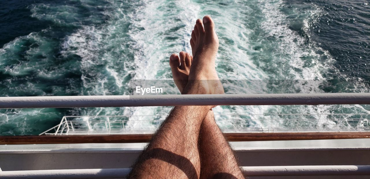 Low section of man relaxing by sea