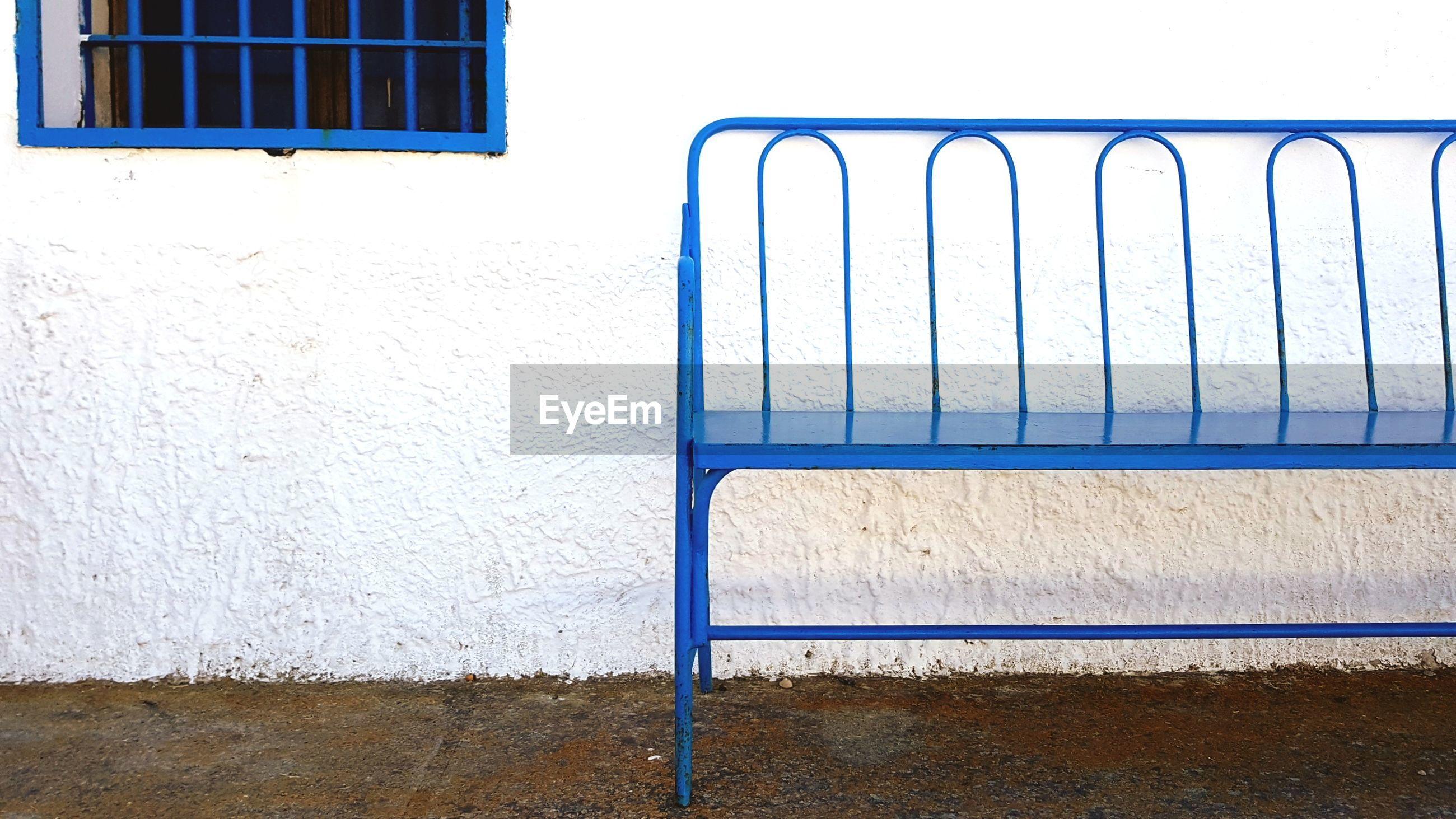 Blue metallic bench against building