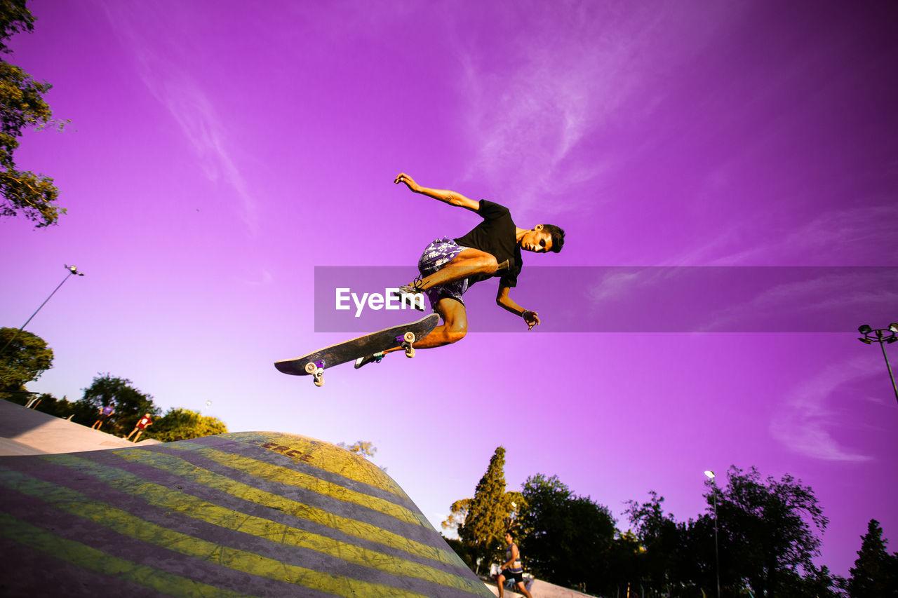 Low angle view of teenager jumping at skatepark