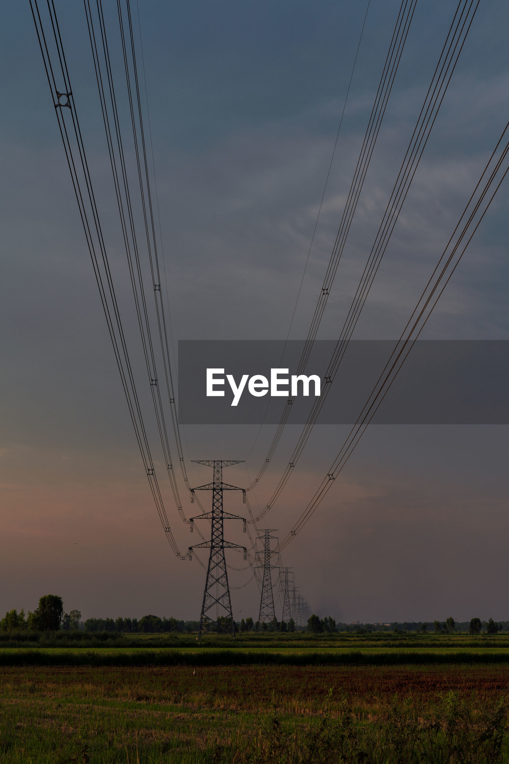 ELECTRICITY PYLON ON FIELD DURING SUNSET
