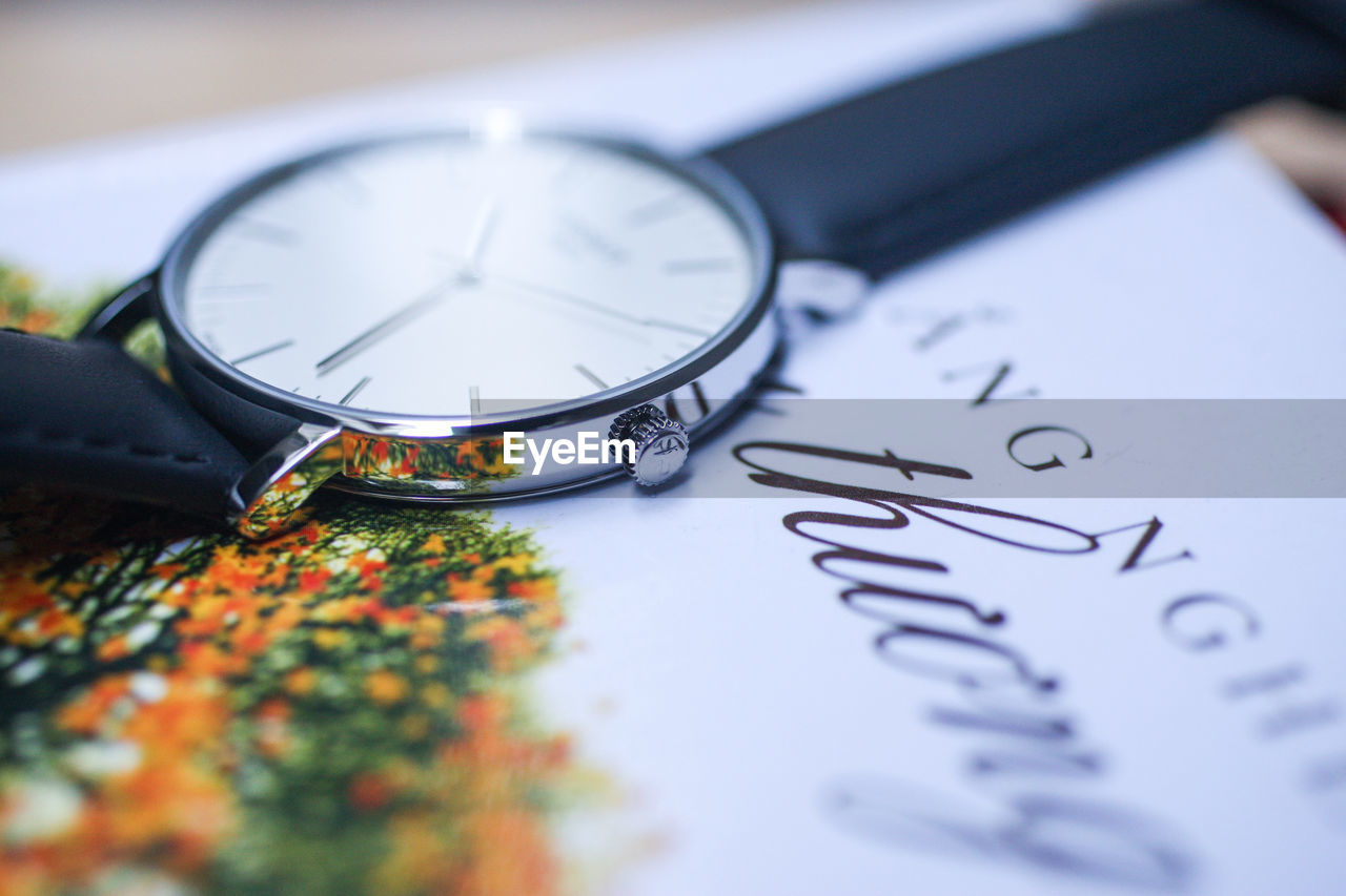 selective focus, time, still life, clock, watch, indoors, text, communication, instrument of time, close-up, no people, table, wristwatch, number, magnifying glass, shape, black color, day, guidance, minute hand, personal accessory