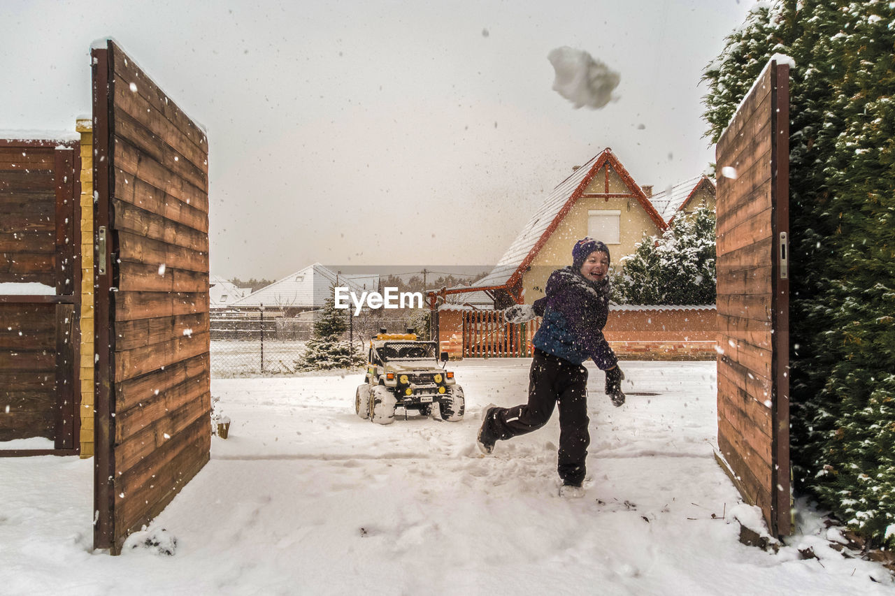 snow, winter, cold temperature, architecture, building exterior, full length, built structure, warm clothing, snowing, one person, real people, building, nature, men, house, clothing, males, day, extreme weather, outdoors