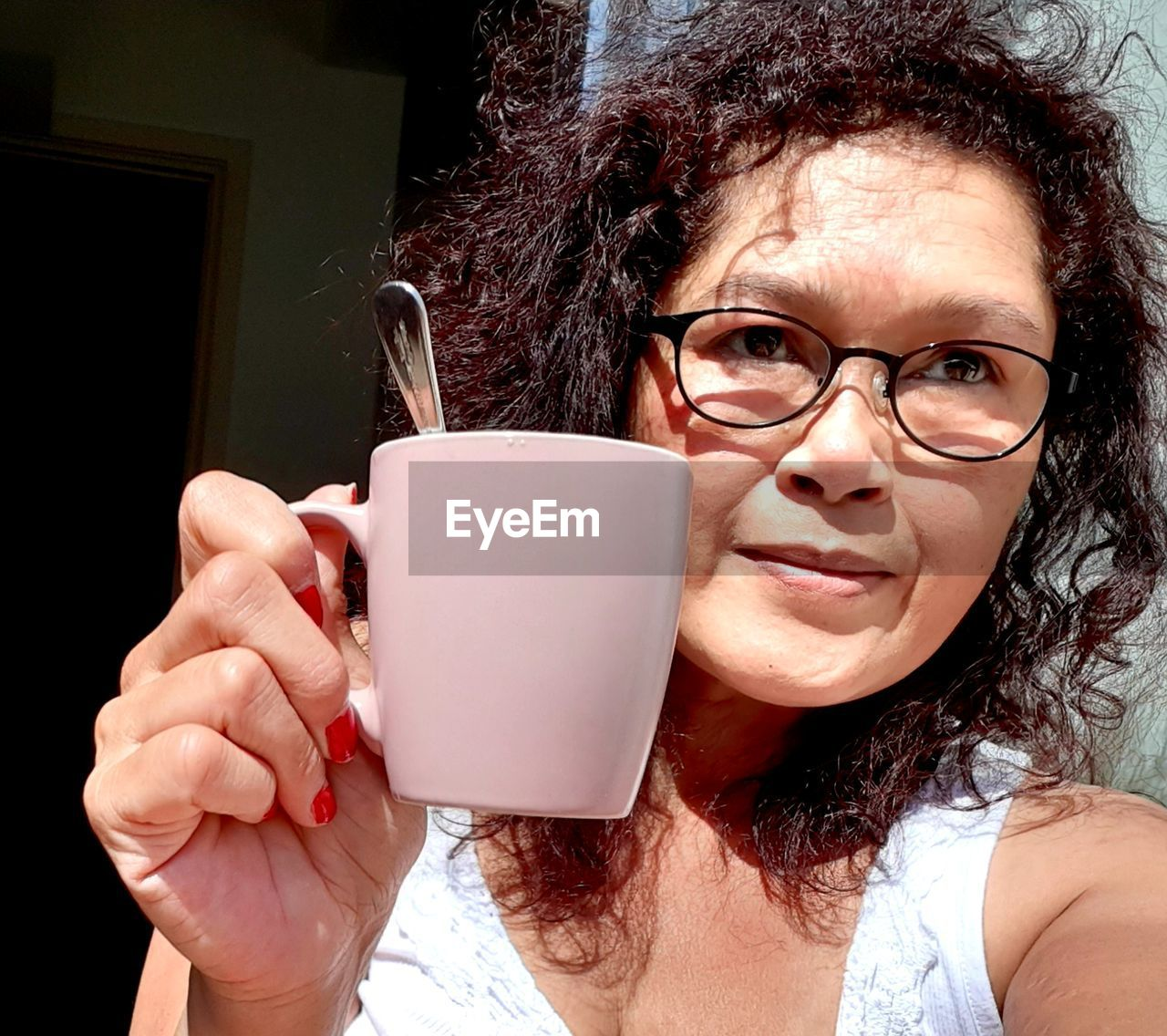 Portrait of smiling woman in eyeglasses holding cup