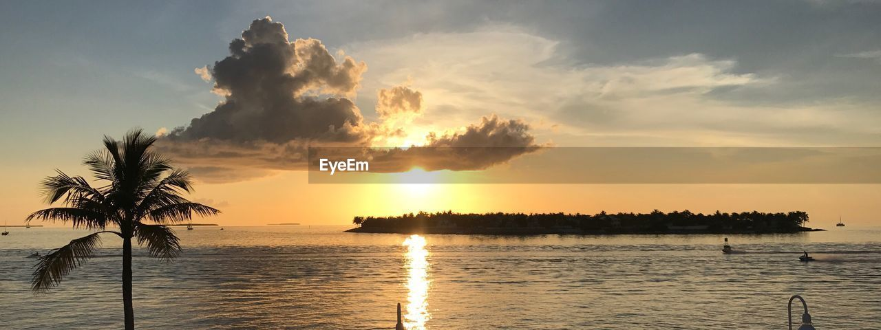 sunset, sea, scenics, beauty in nature, tranquility, sky, water, nature, tranquil scene, idyllic, palm tree, no people, cloud - sky, beach, sun, silhouette, outdoors, tree, vacations, horizon over water