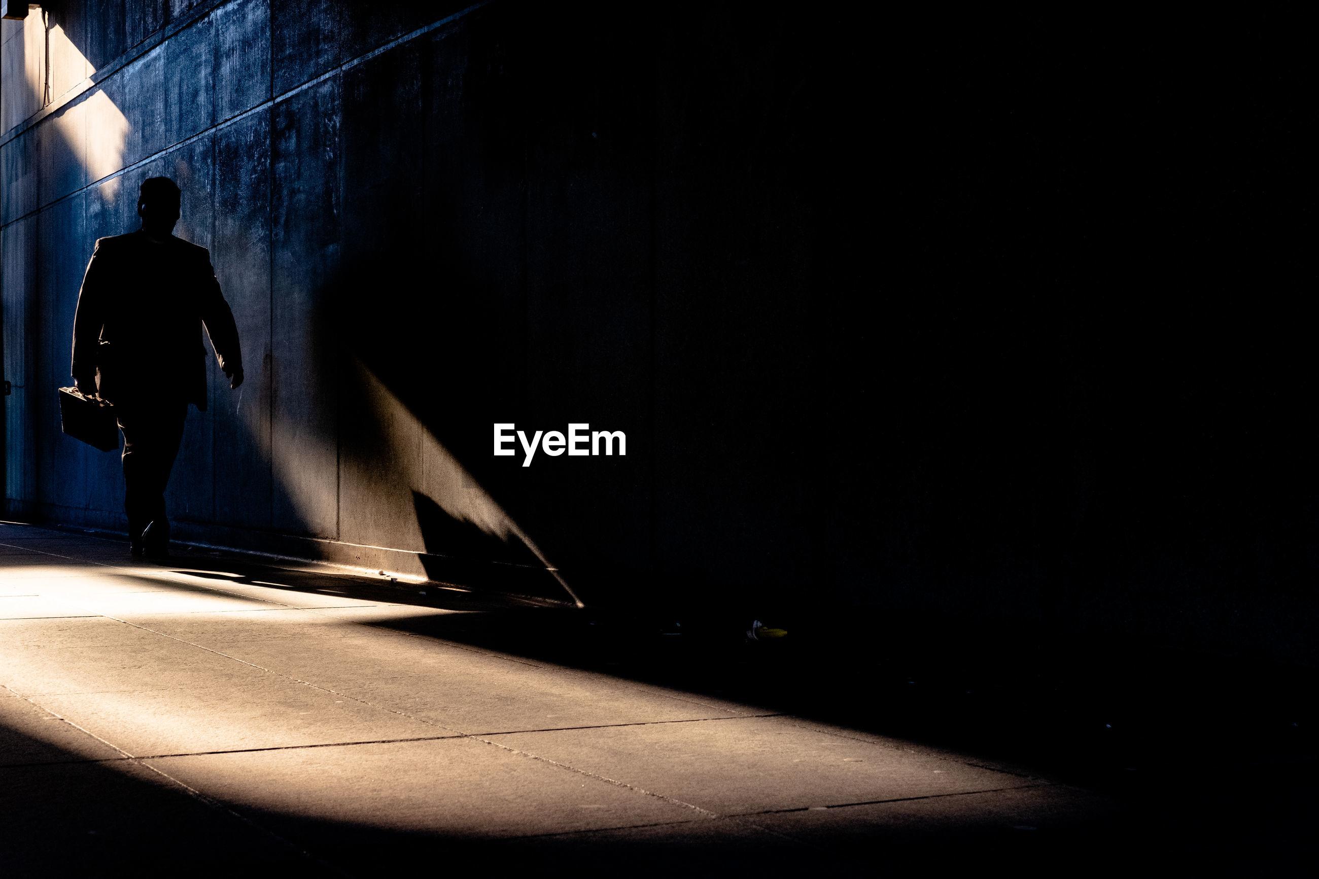 REAR VIEW OF MAN WALKING ON FOOTPATH AT ILLUMINATED WALL