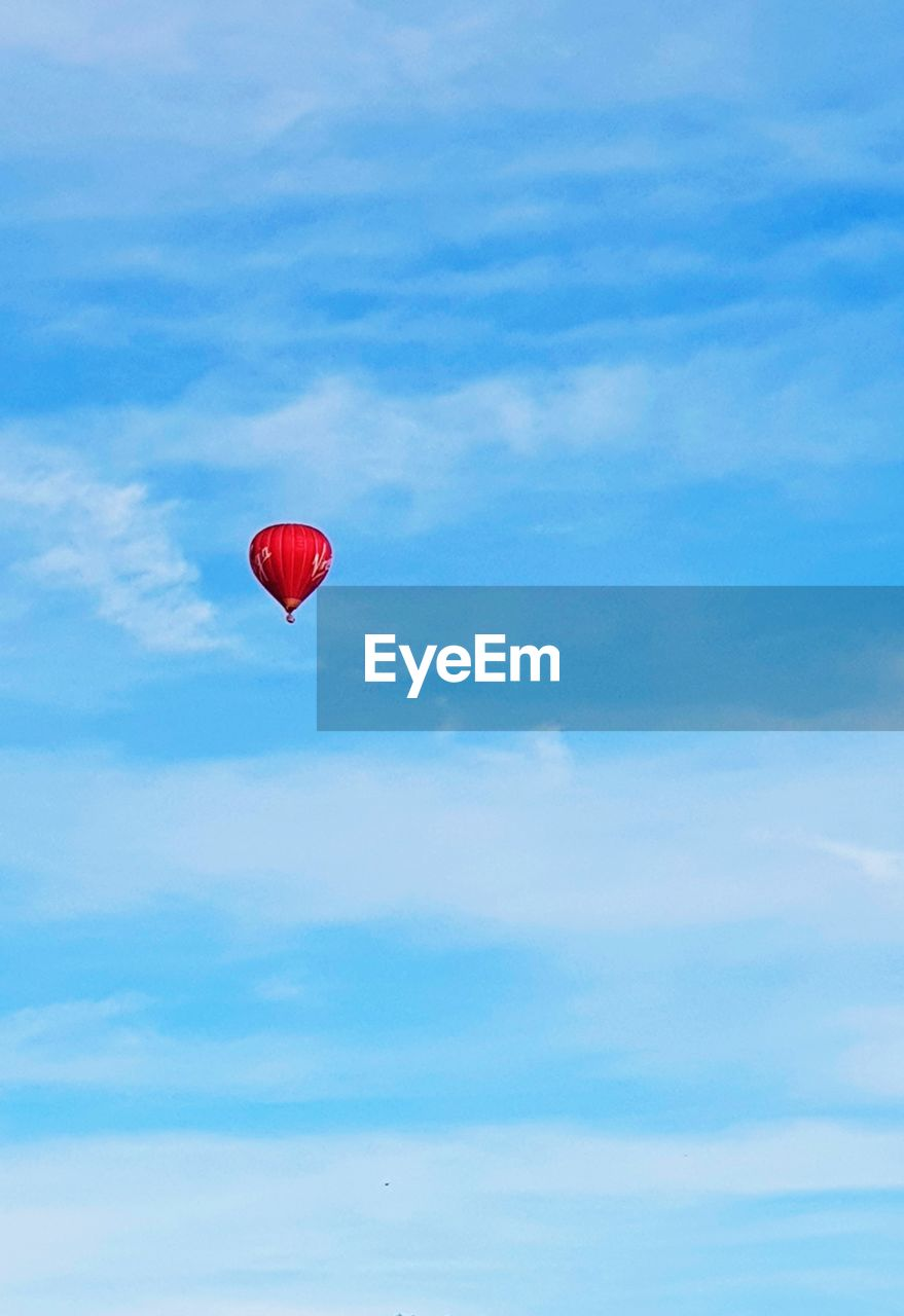 sky, red, cloud - sky, low angle view, mid-air, balloon, flying, adventure, nature, day, beauty in nature, blue, no people, extreme sports, transportation, outdoors, freedom, tranquility, parachute, scenics - nature