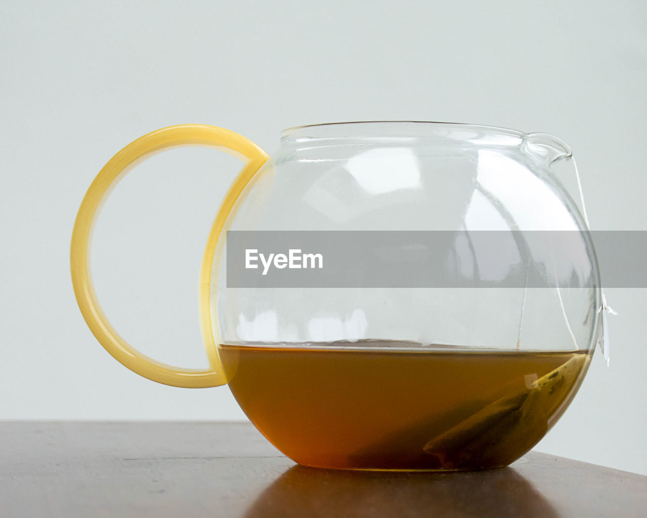 Close-up of tea in kettle on table against white background