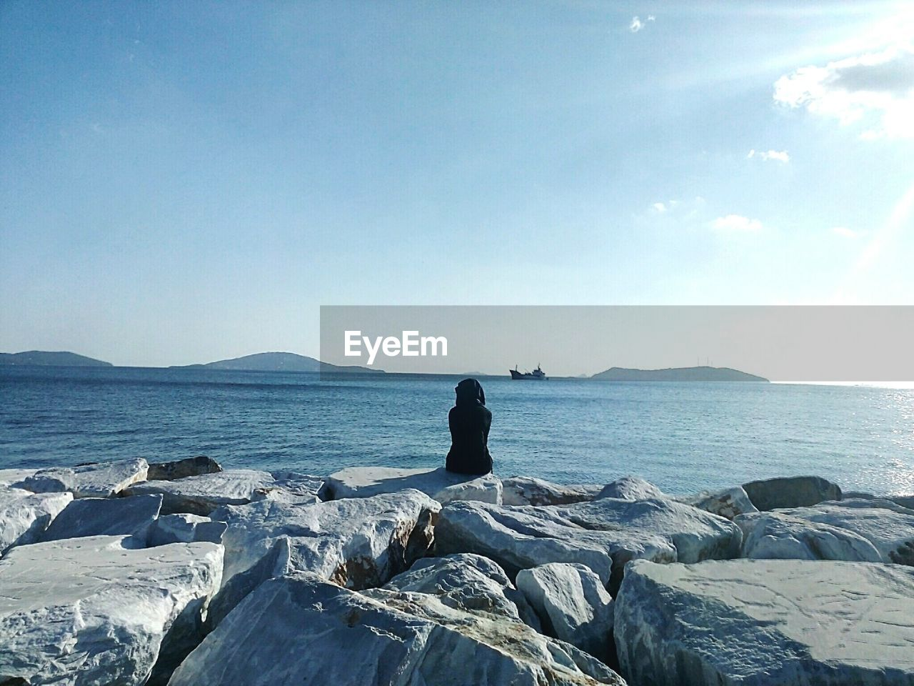 Rear View Of Woman Sitting On Rock By Sea Against Clear Sky