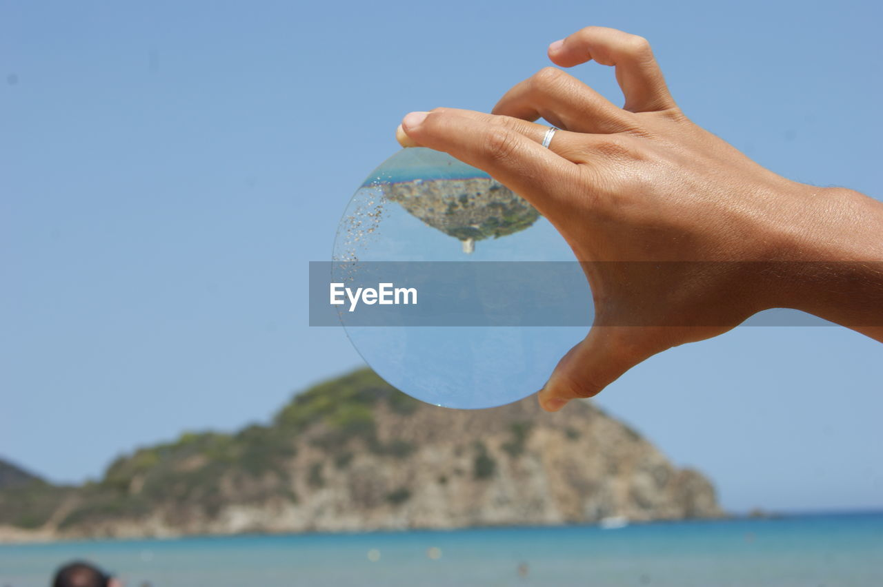 Cropped image of hand holding crystal ball with reflection against blue sky