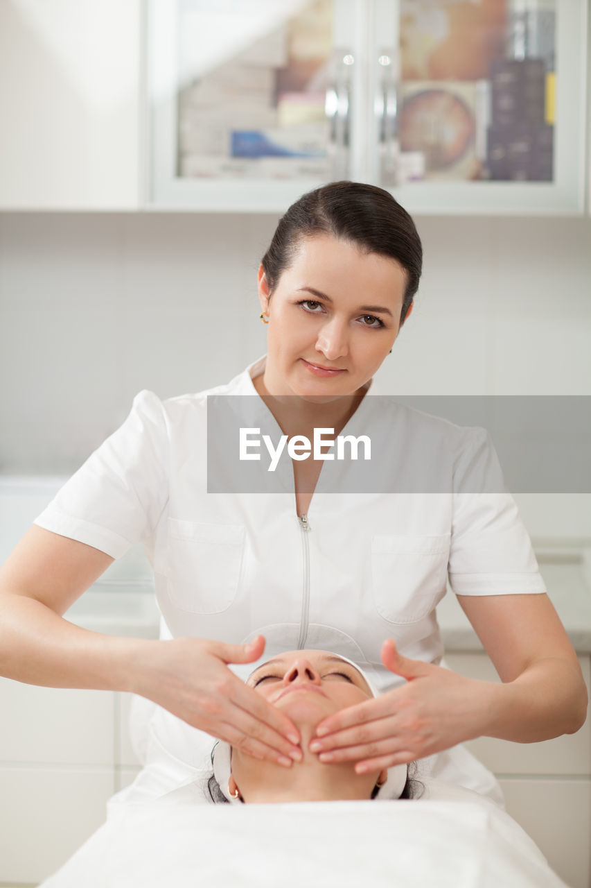 women, young adult, portrait, front view, young women, adult, beauty spa, looking at camera, indoors, human hand, wellbeing, beauty treatment, two people, occupation, waist up, beautician, beauty, holding, beautiful woman, hand, spa, manicure, luxury, human face