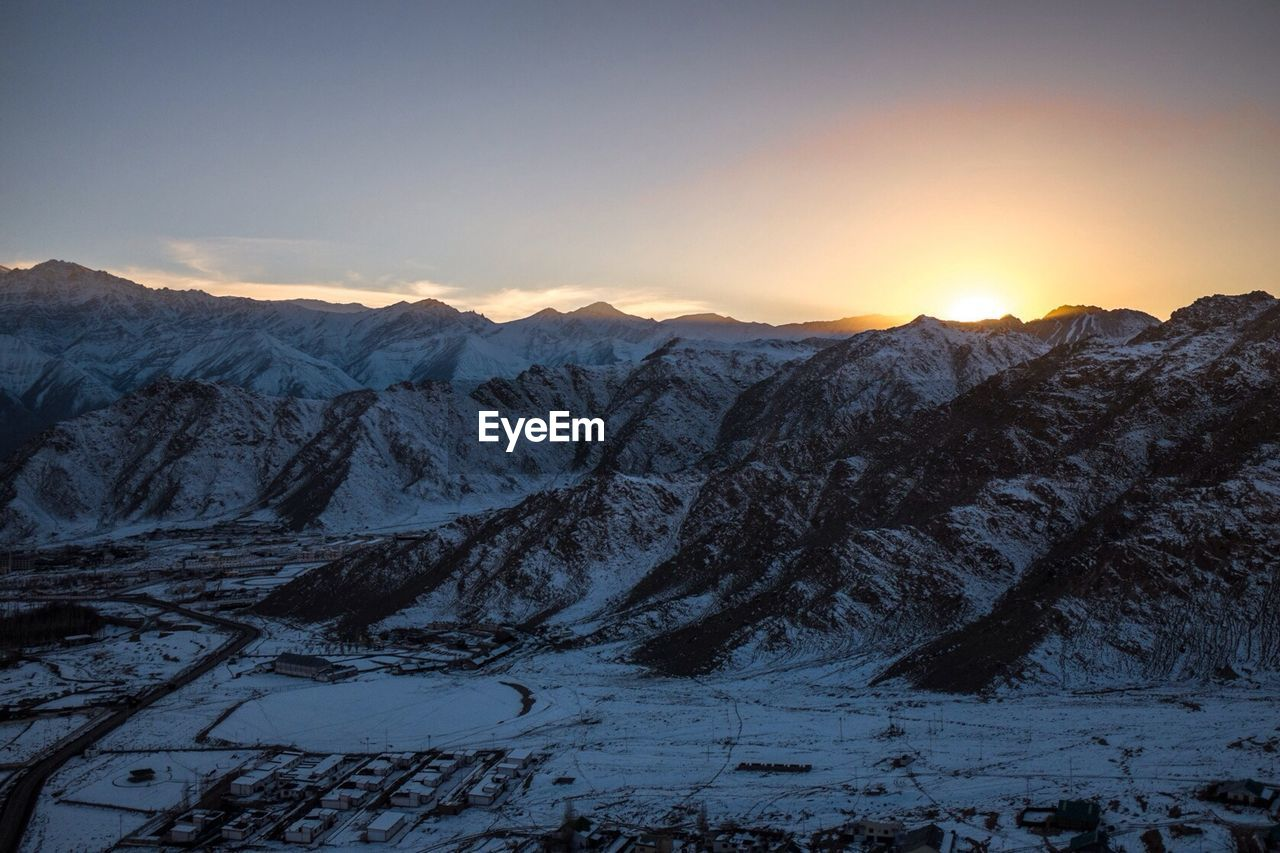 Snow covered mountains against sky at sunset