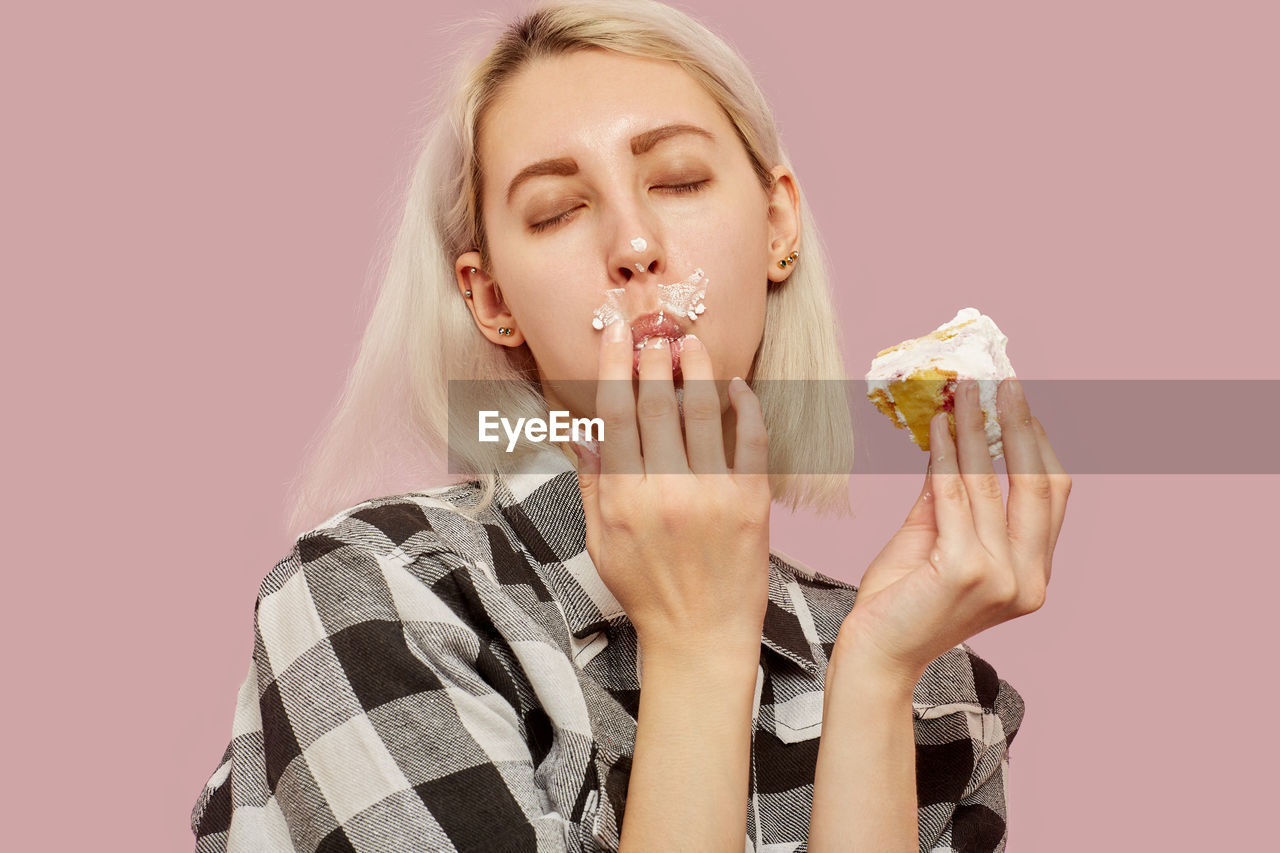 PORTRAIT OF YOUNG WOMAN EATING ICE CREAM AGAINST GRAY BACKGROUND