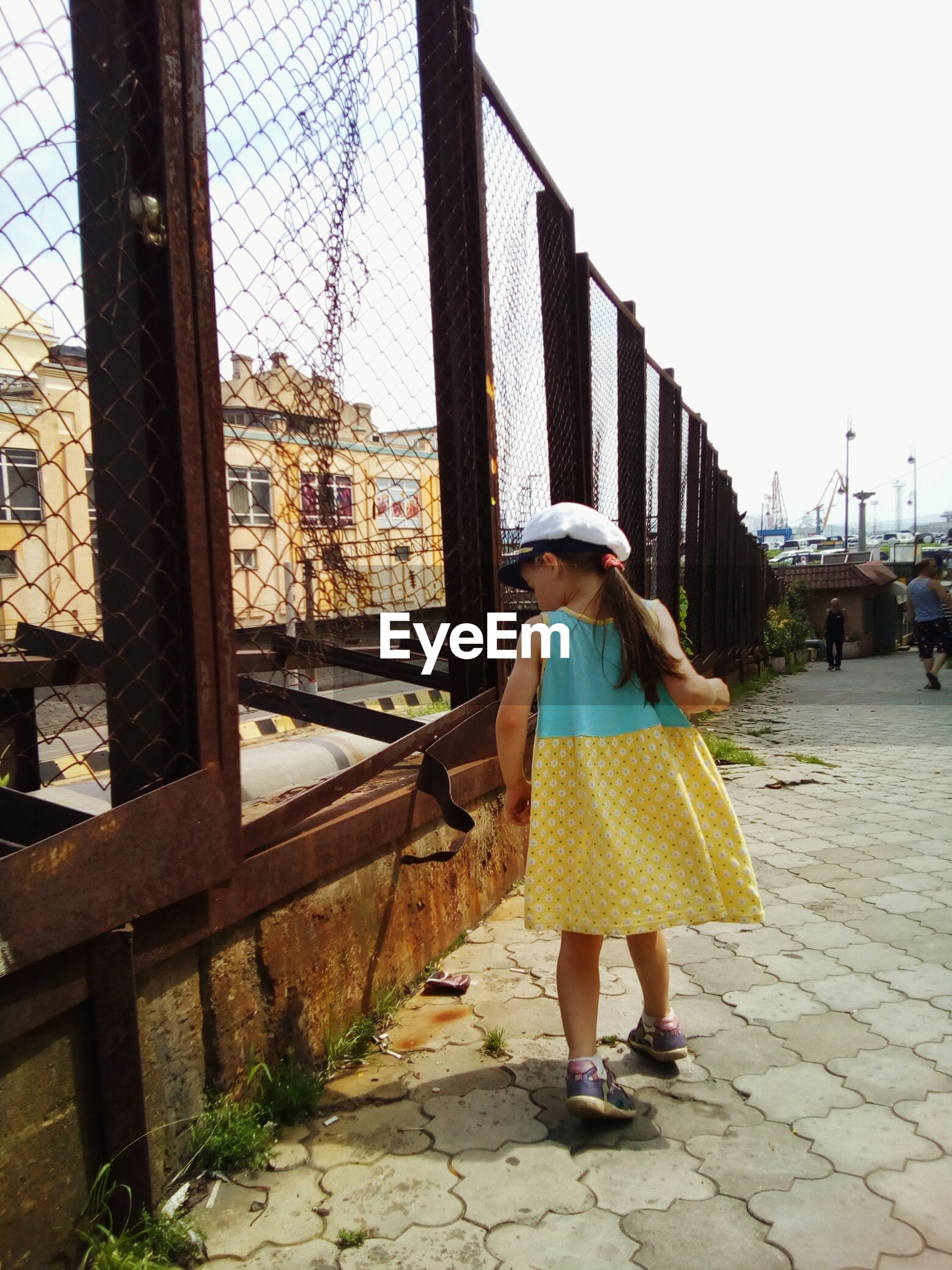 Rear view of girl walking by damaged chainlink fence