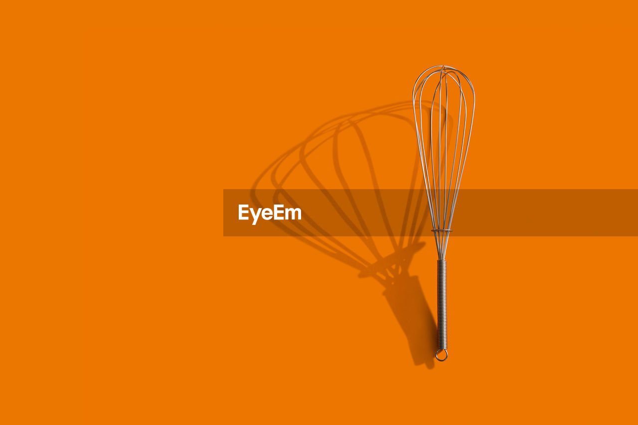 Directly above view of wire whisk over orange background
