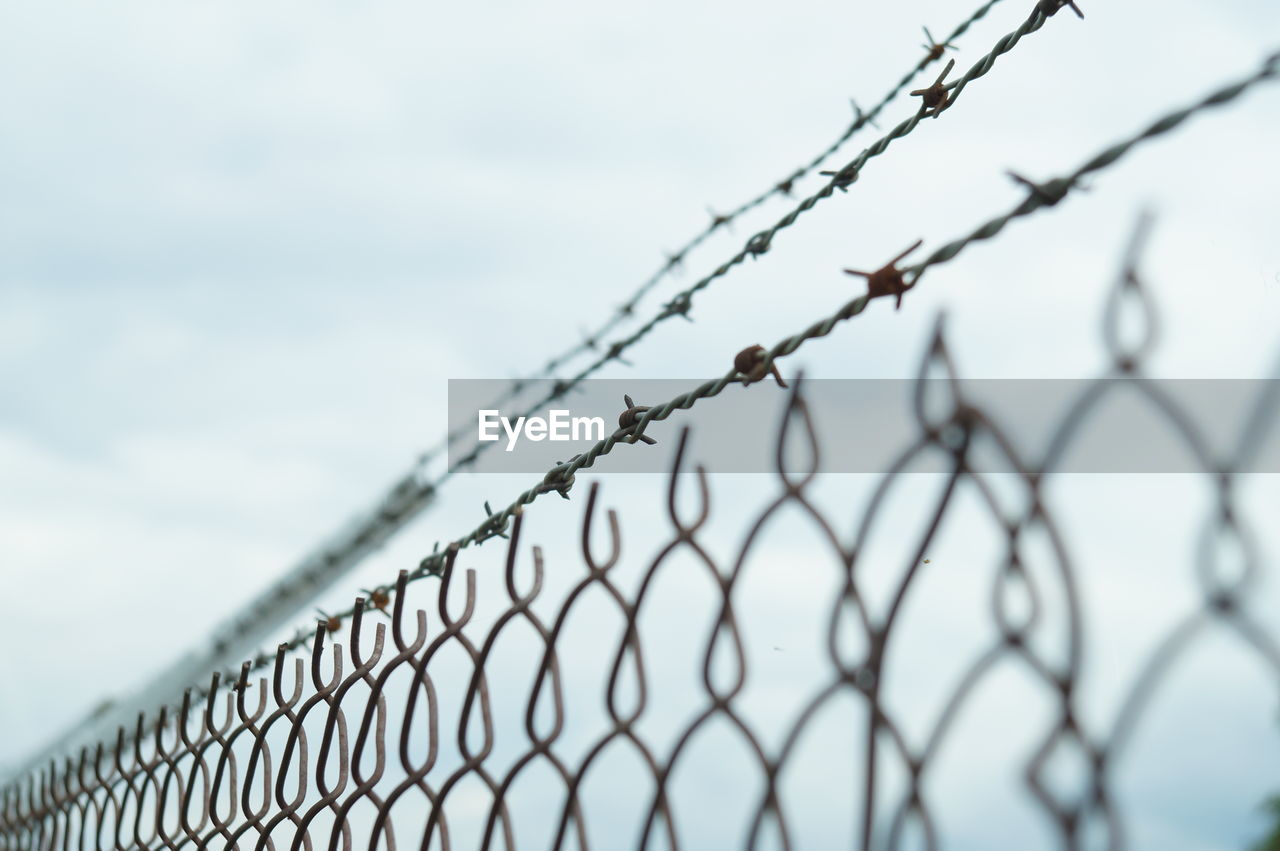 CLOSE-UP OF FENCE AGAINST SKY