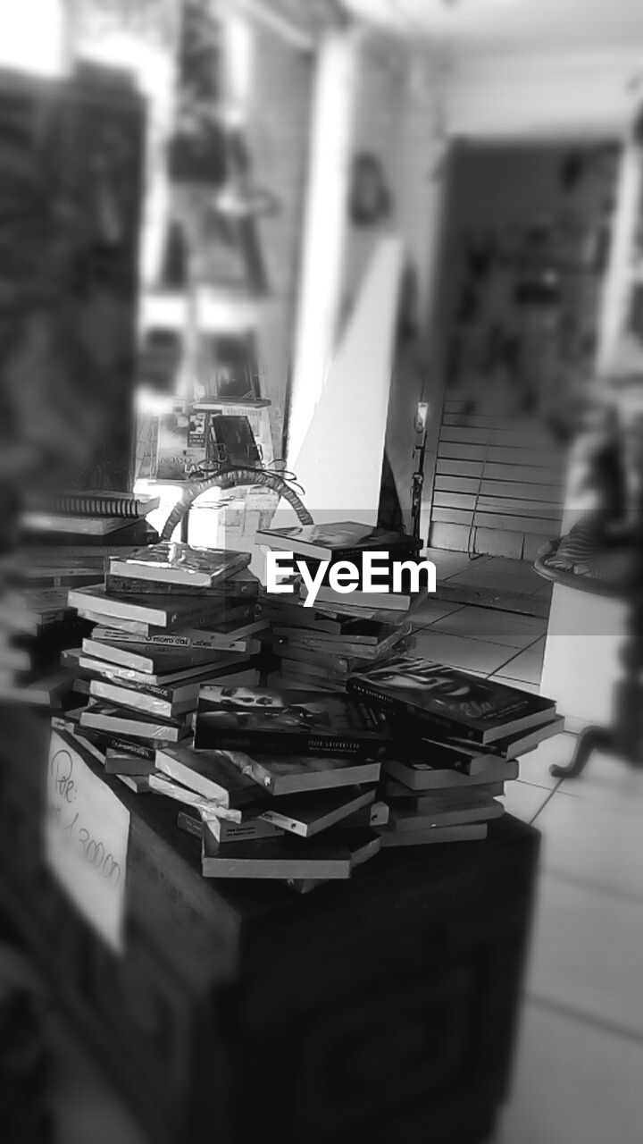 indoors, selective focus, stack, desk, table, no people, large group of objects, close-up, day, bookshelf