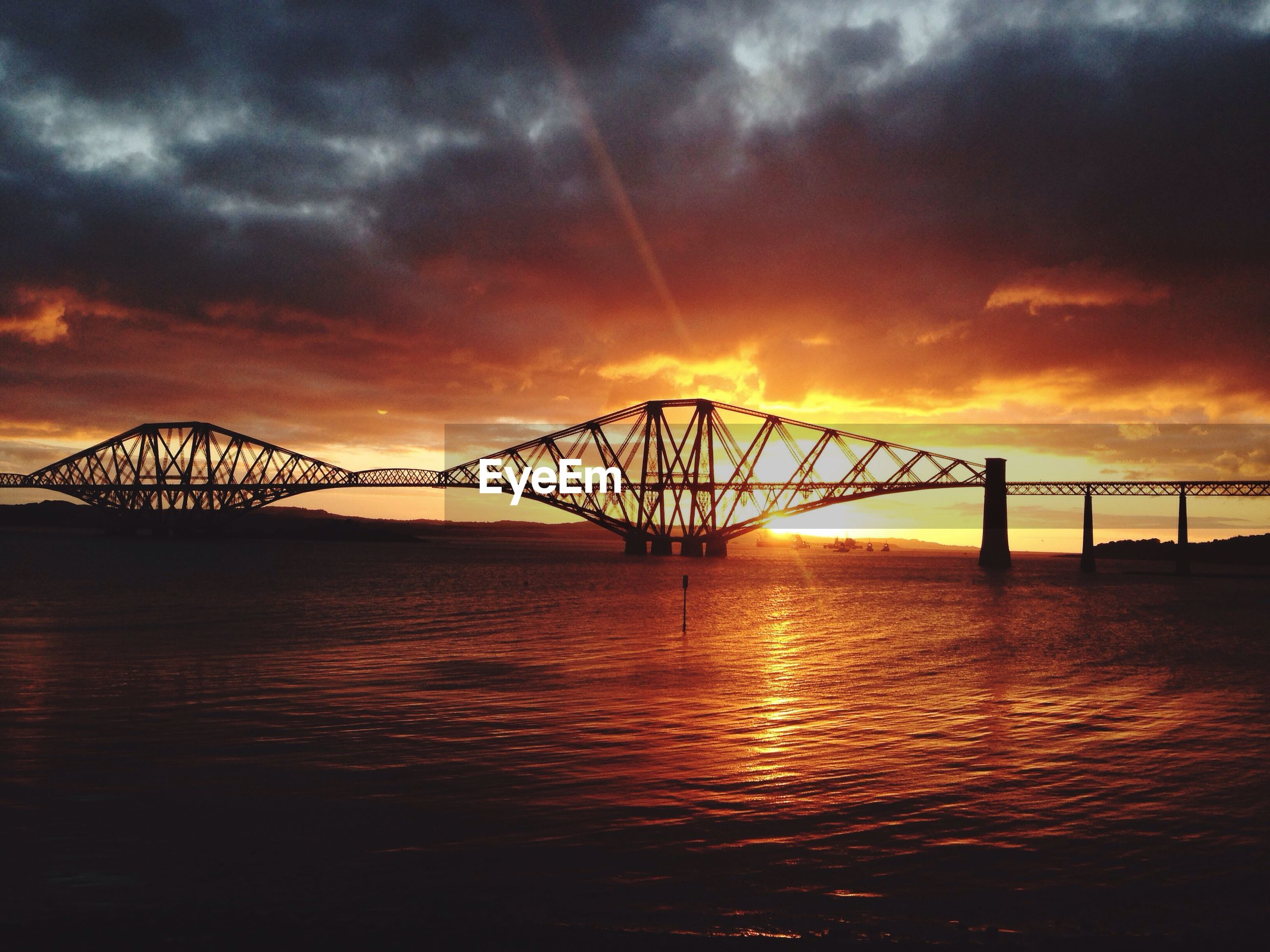 Silhouette forth bridge over river against cloudy sky during sunset
