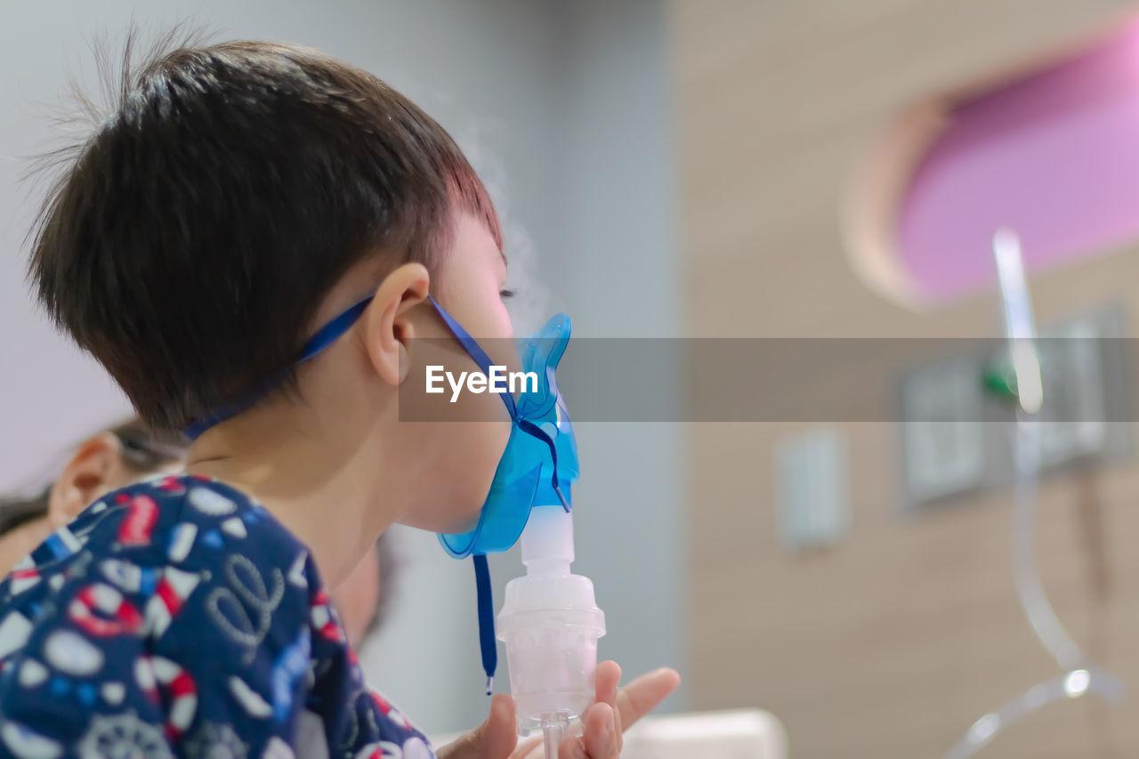 Boy wearing oxygen mask in hospital
