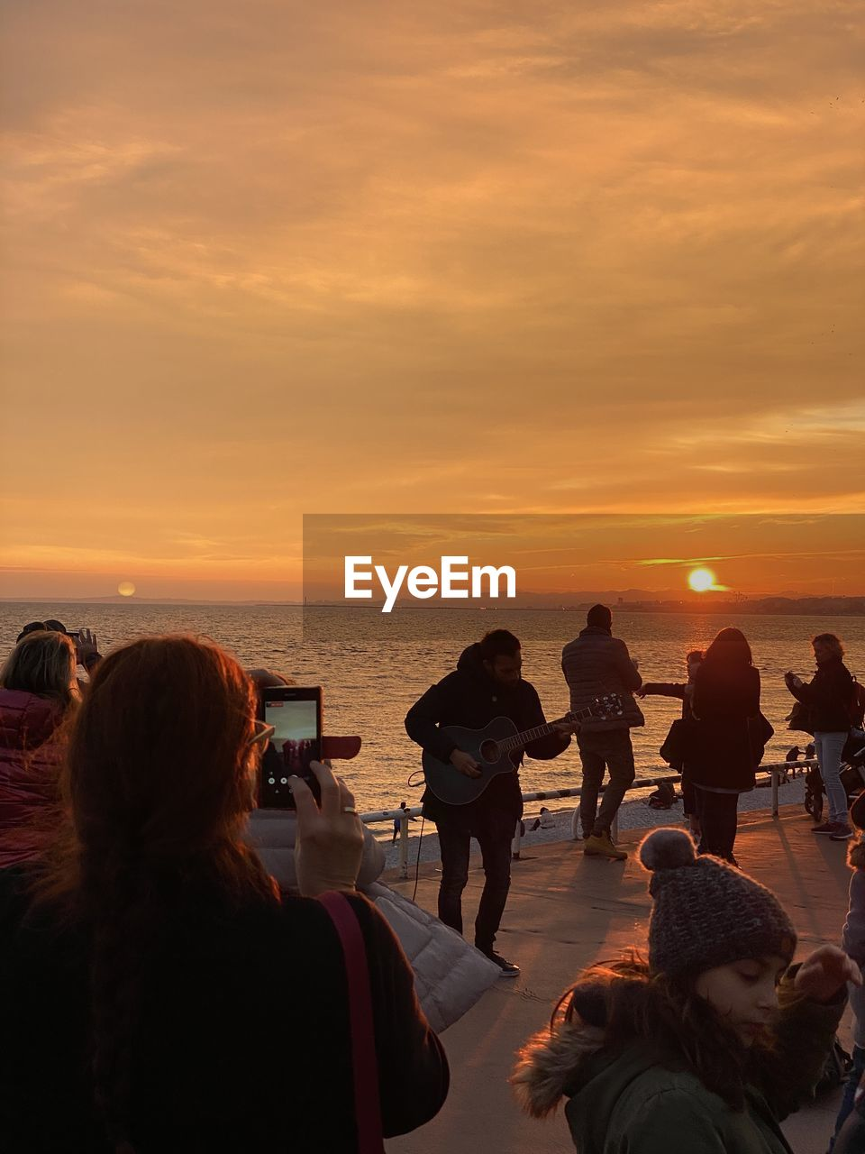 sunset, water, group of people, sea, sky, real people, horizon over water, orange color, women, beach, beauty in nature, leisure activity, horizon, adult, lifestyles, cloud - sky, land, scenics - nature, rear view, outdoors