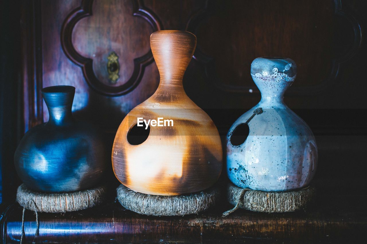 Close-Up Of Pottery Jugs On Wooden Shelf