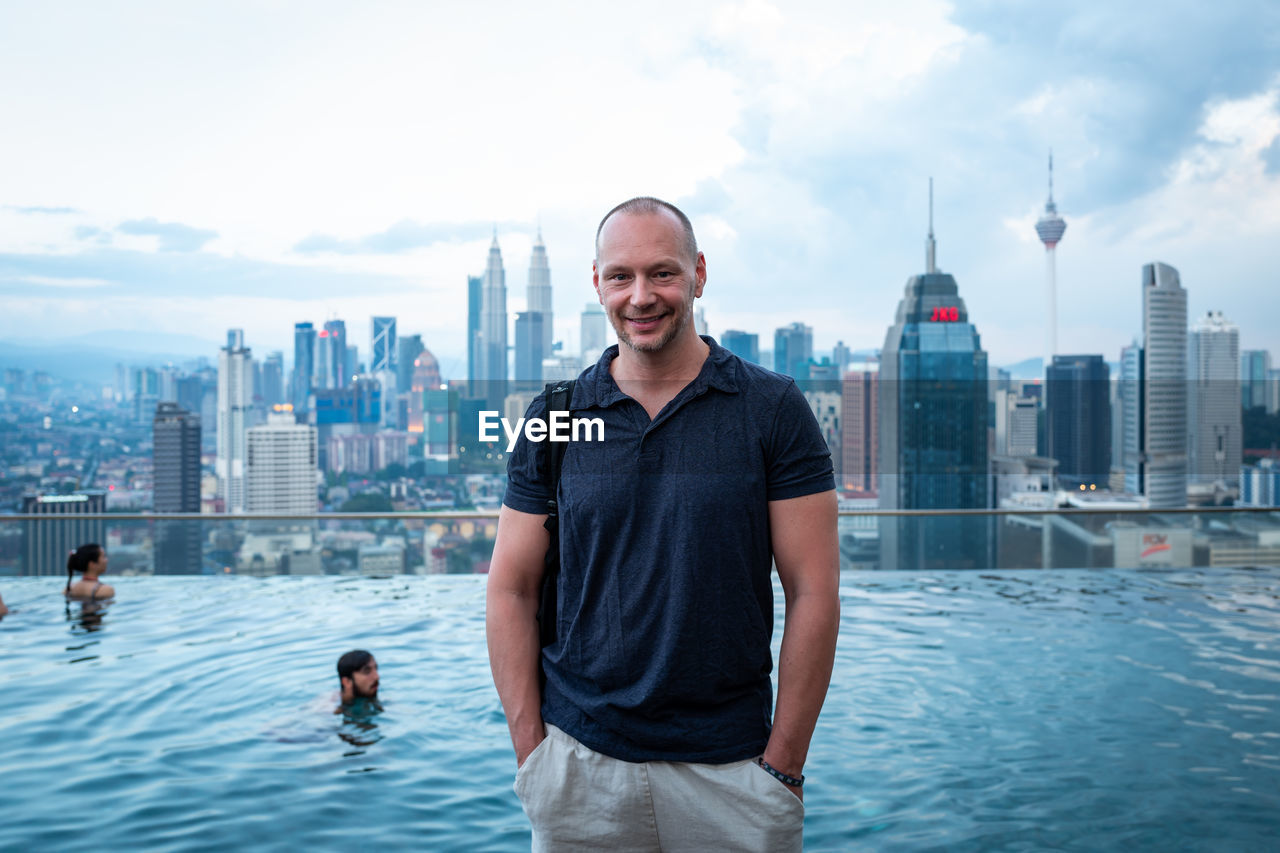 architecture, building exterior, city, built structure, smiling, water, standing, men, sky, nature, real people, looking at camera, one person, cityscape, leisure activity, building, office building exterior, waist up, casual clothing, tall - high, skyscraper, outdoors, swimming pool