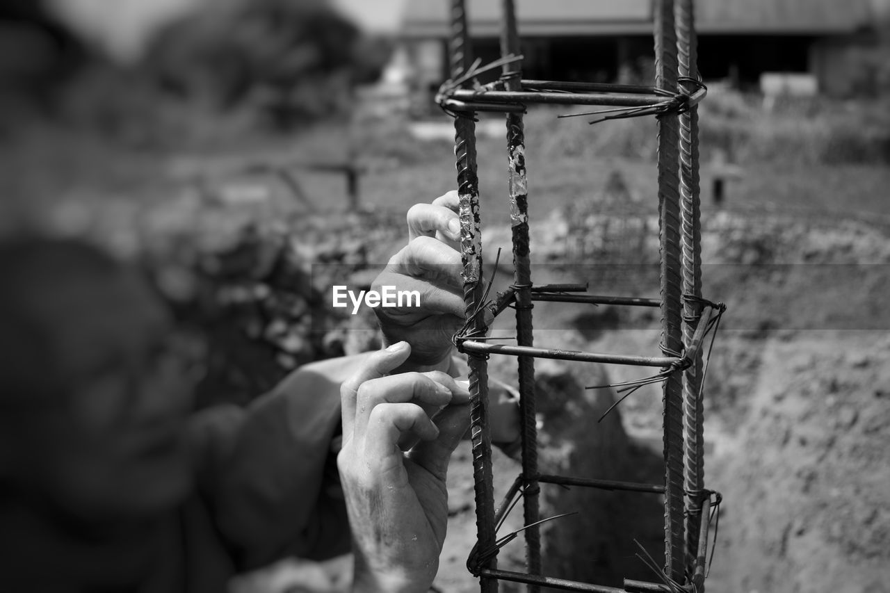 focus on foreground, day, selective focus, outdoors, metal, real people, holding, close-up, people, human hand, human body part, hand, nature, unrecognizable person, chain, connection, leisure activity, strength