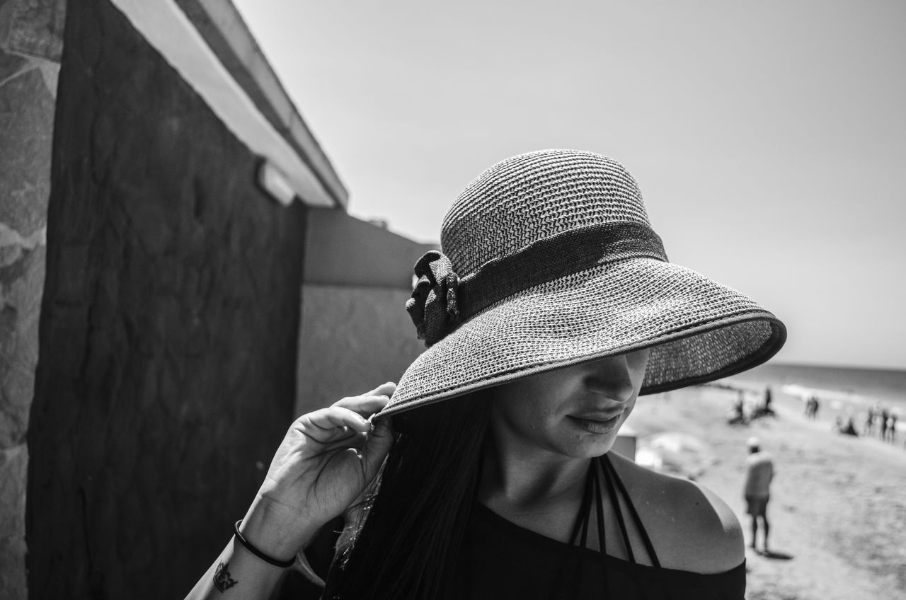Close-Up Of Young Woman Wearing Hat At Beach Against Sky