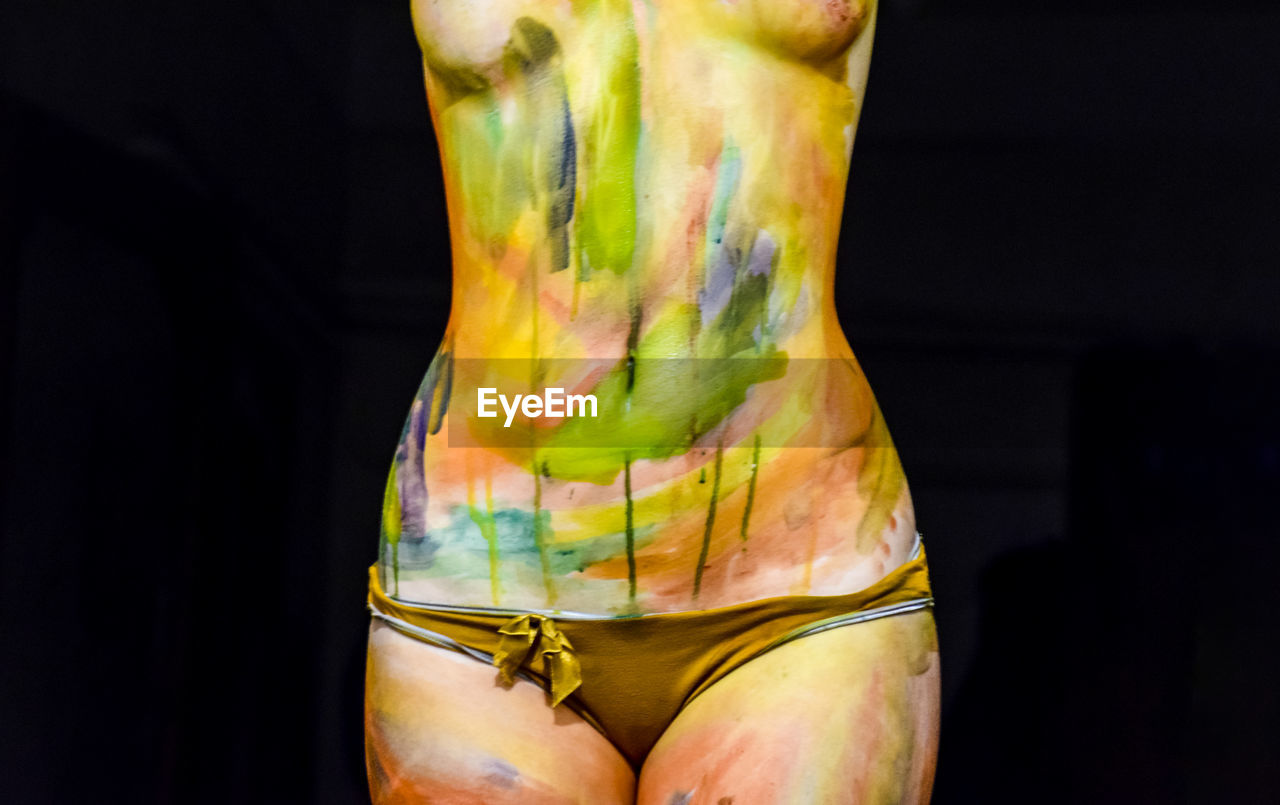 Midsection of naked woman with colorful body paint against black background