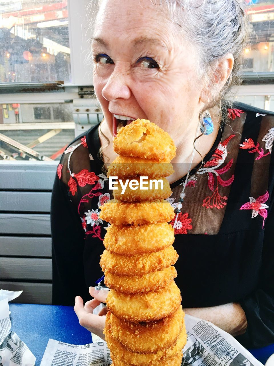 Close-up of happy mature woman eating food