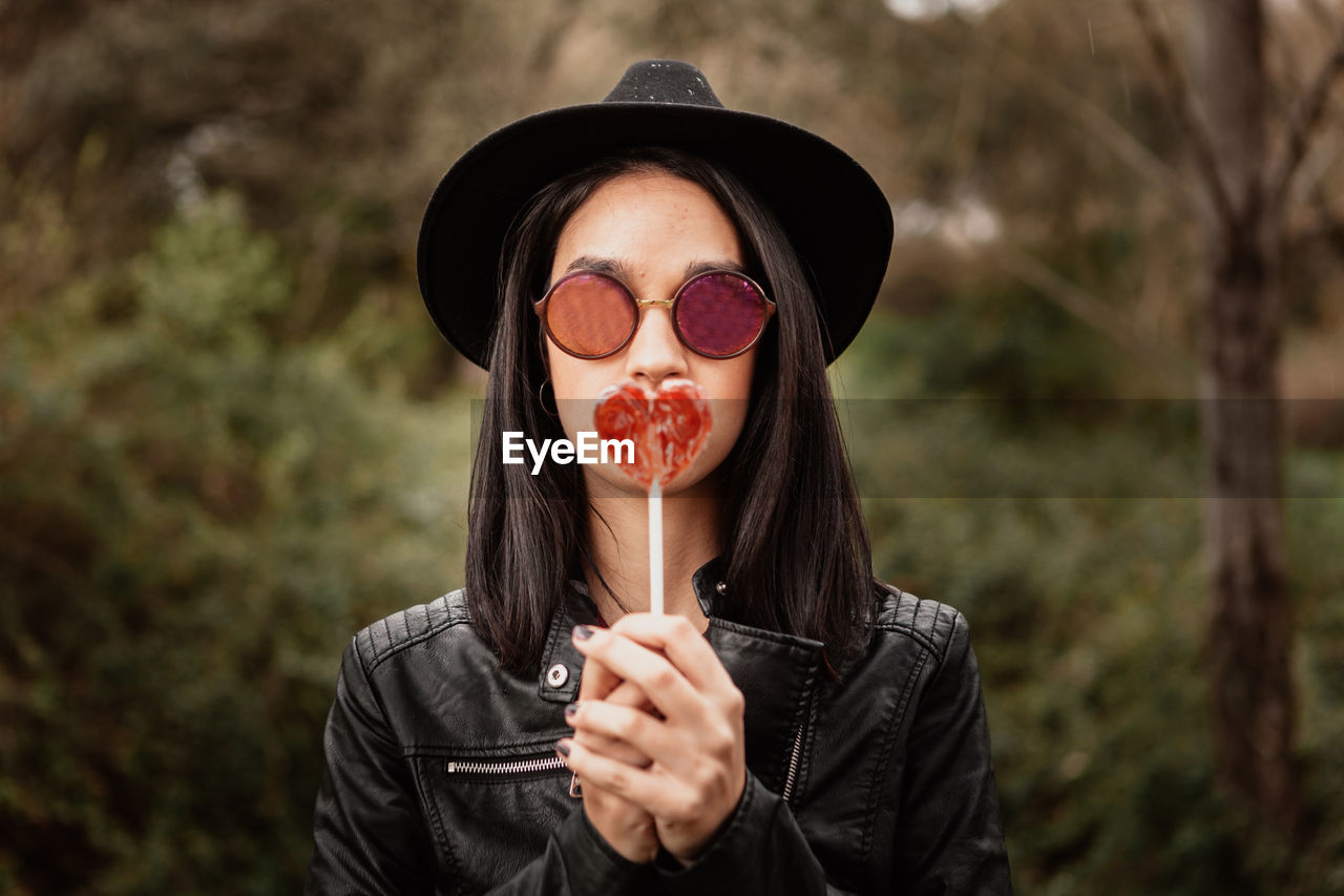 Portrait of woman wearing sunglasses holding heart shaped candy