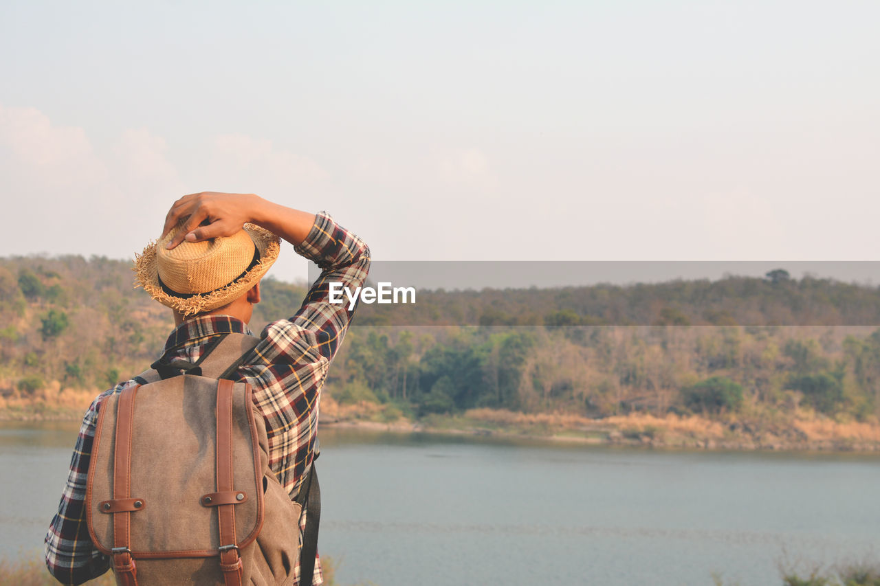 Rear View Of Man By Water Against Sky