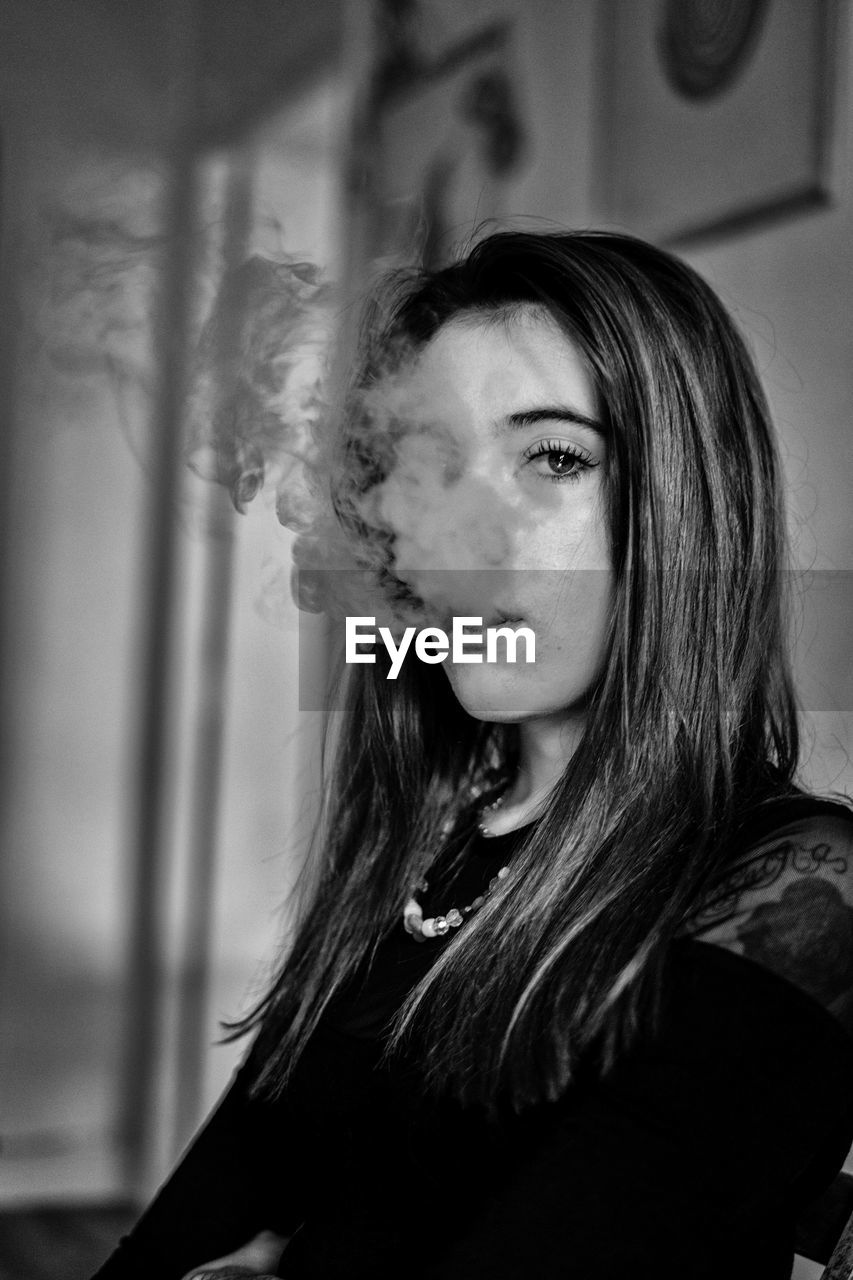 Portrait of woman exhaling smoke at home